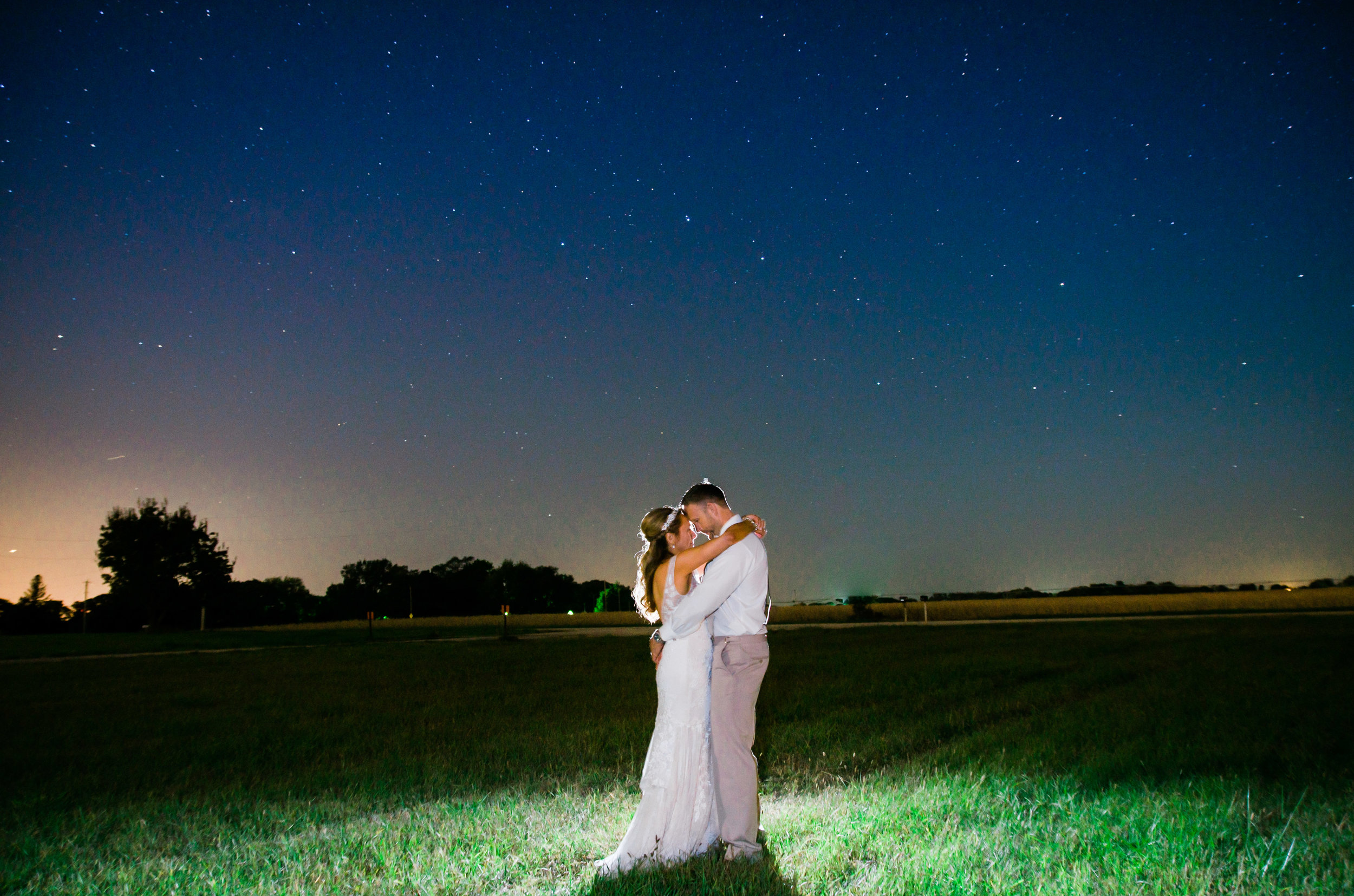 A photograph of a bride and groom at night with stars. The bride and groom are standing in a field in the country at a wedding venue just outside of Omaha.