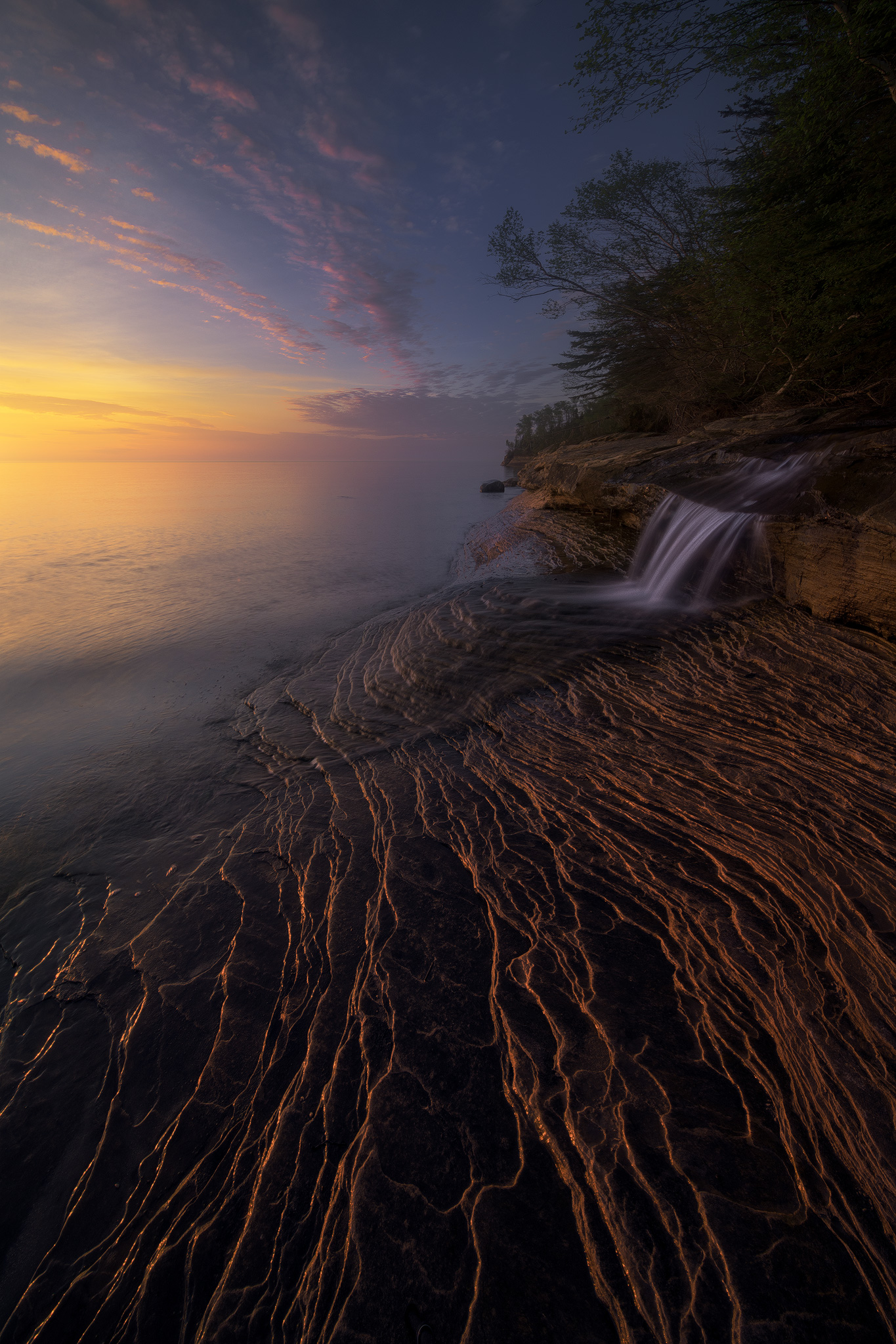 """""""Northern Reach""""    Waterfall on the shores of Lake Superior.Irix 11mm at f/16, 1 second. In this case 11mm was really helpful, as the clouds were arcing high overhead, and the prominent foreground ridges lended themselves well to the wide view, adding lots of depth to the scene. I was probably less than 10 feet from the waterfall!"""