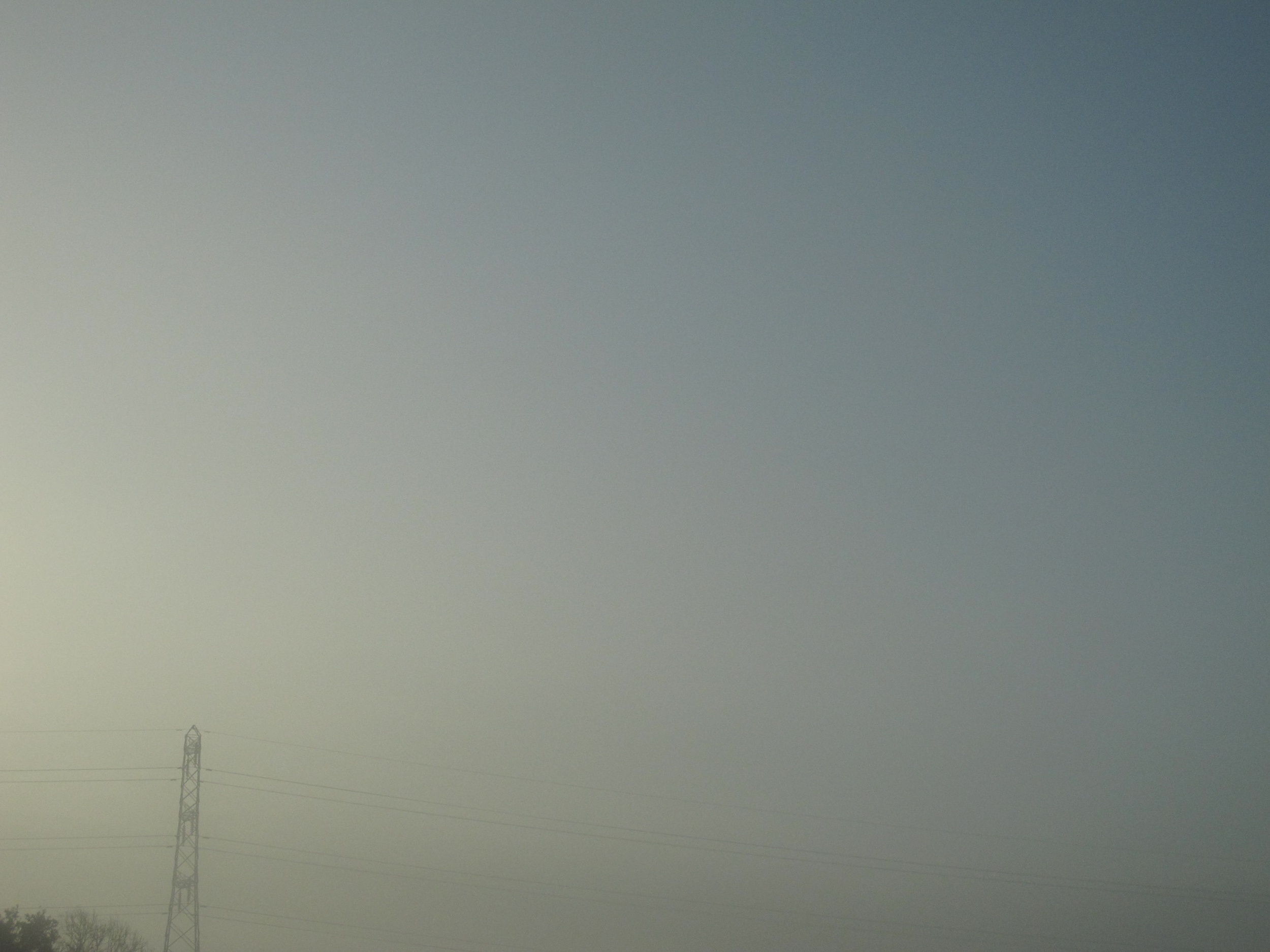 Transmission tower in mist at sunrise