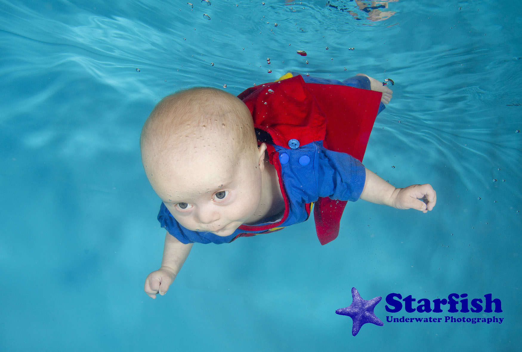 William Jones at 4 months, swimming underwater, two days before going into hospital for open heart surgery. His mum Susan thinks he's a Superman for surviving everything he has been through.William Jones, was born with Down's Syndrome and a hole in his heart.   Baby swimming lessons with Aquatots Swim School, at a pool in Cirencester, have dramatically improved his muscle development and overall development. The strength he has built up through swimming prepared him for the open heart surgery to repair the hole in his heart and also helped him cope with complications following surgery.Photo by Lucy Ray/Starfish Underwater Photography