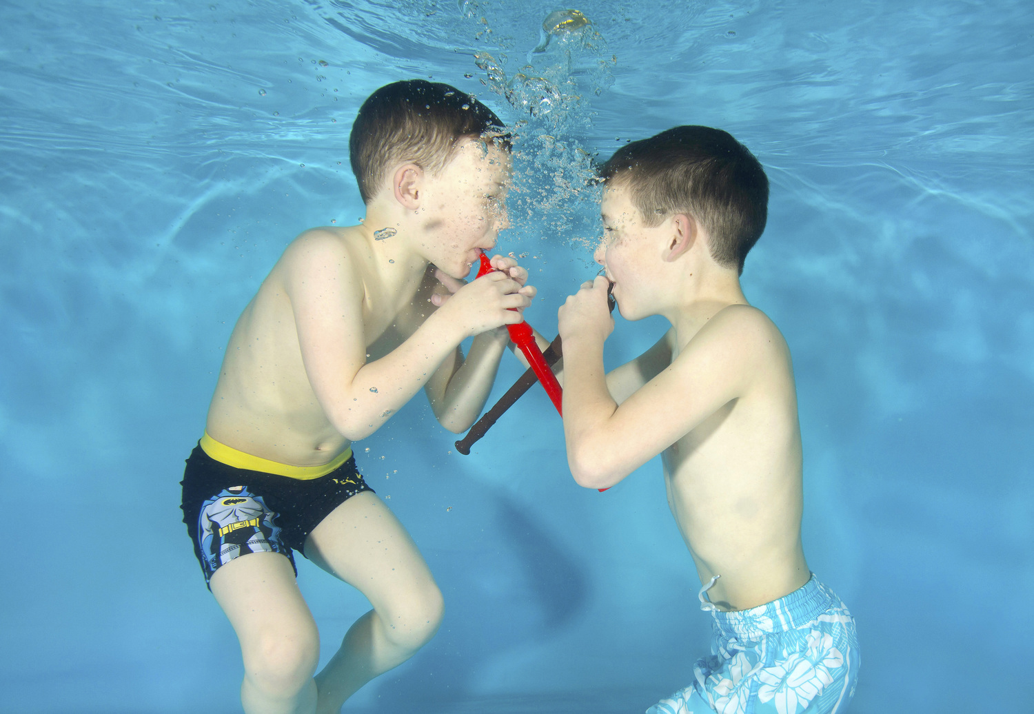Brothers Harley Magee, 8 and Zack Magee, 6, play  underwater recorders at a Starfish Underwater Photography photo shoot with Tadpole Tots swim school, in Farnham, Surrey.  Starfish Underwater Photography holds underwater photo shoots in many locations around England. All babies and children taking part have practiced underwater submersions and are taking swimming lessons.   Photo by Lucy Ray/www.starfishunderwaterphotography.com