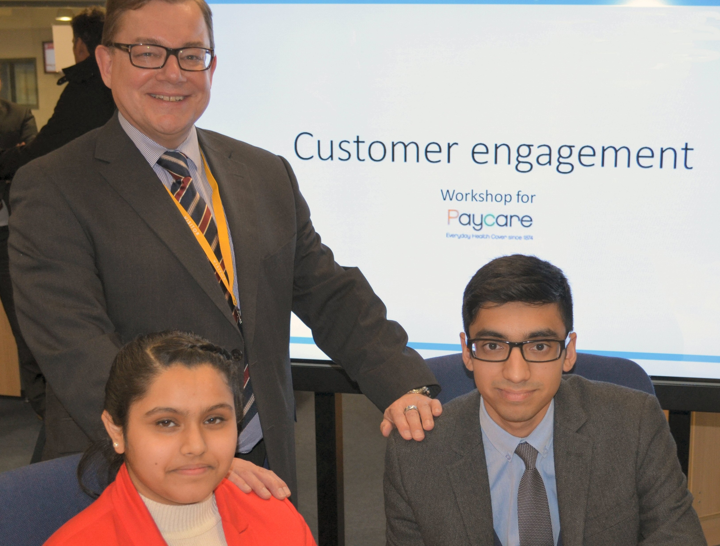 Year 13 Economic students Quais Khan and Amanjeet Maheru with Paycare chief executive, Kevin Rogers.