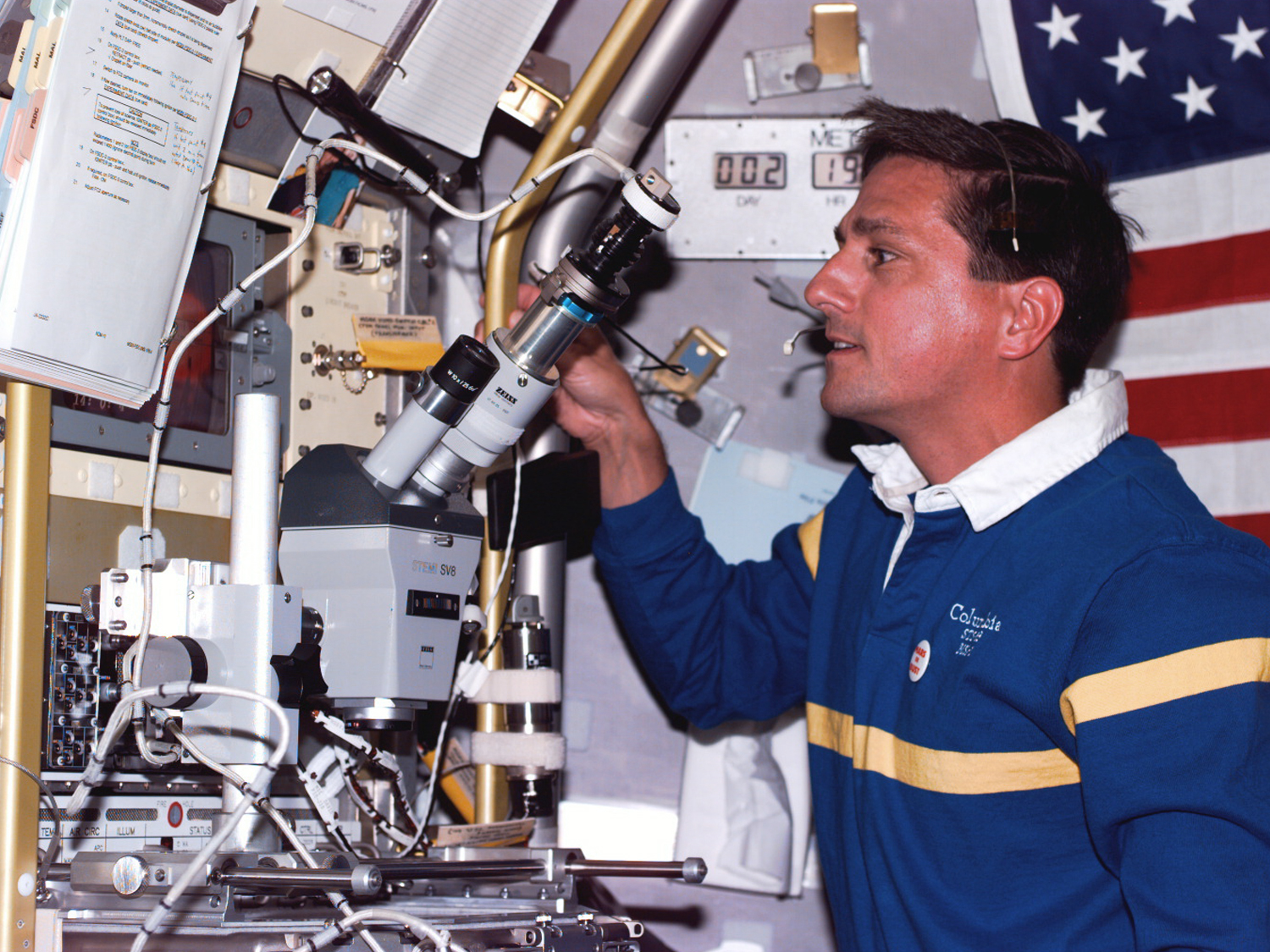 Using microscope at the microgravity glove box facility in Spacelab.