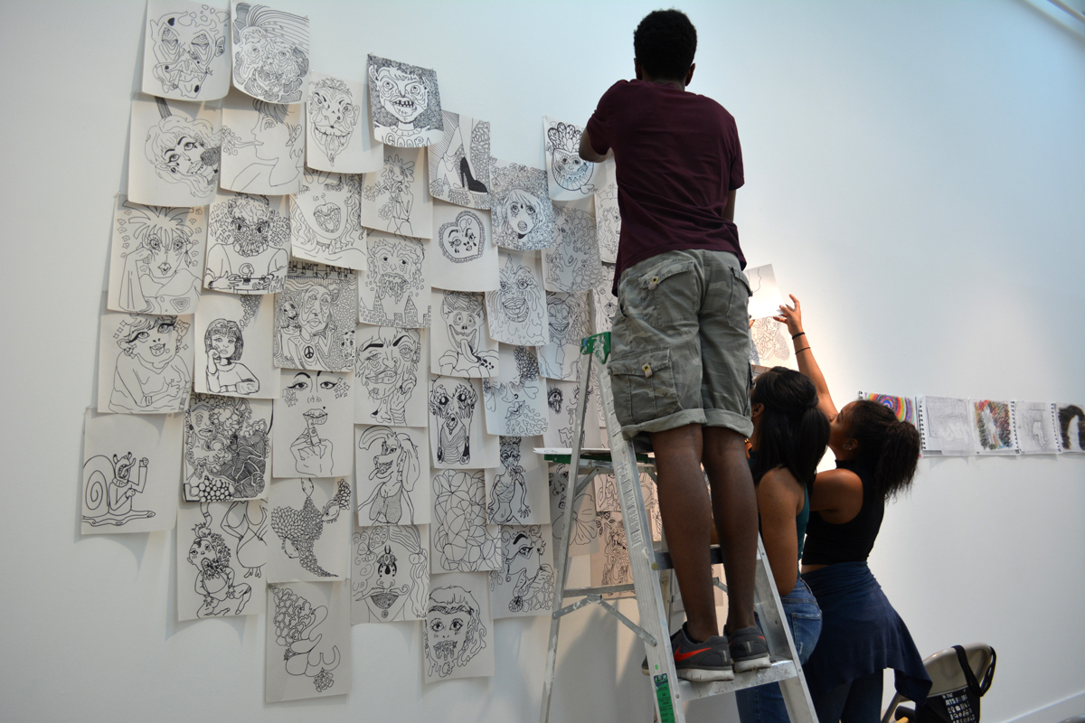 jumpstART artists installing their work in the CUE gallery