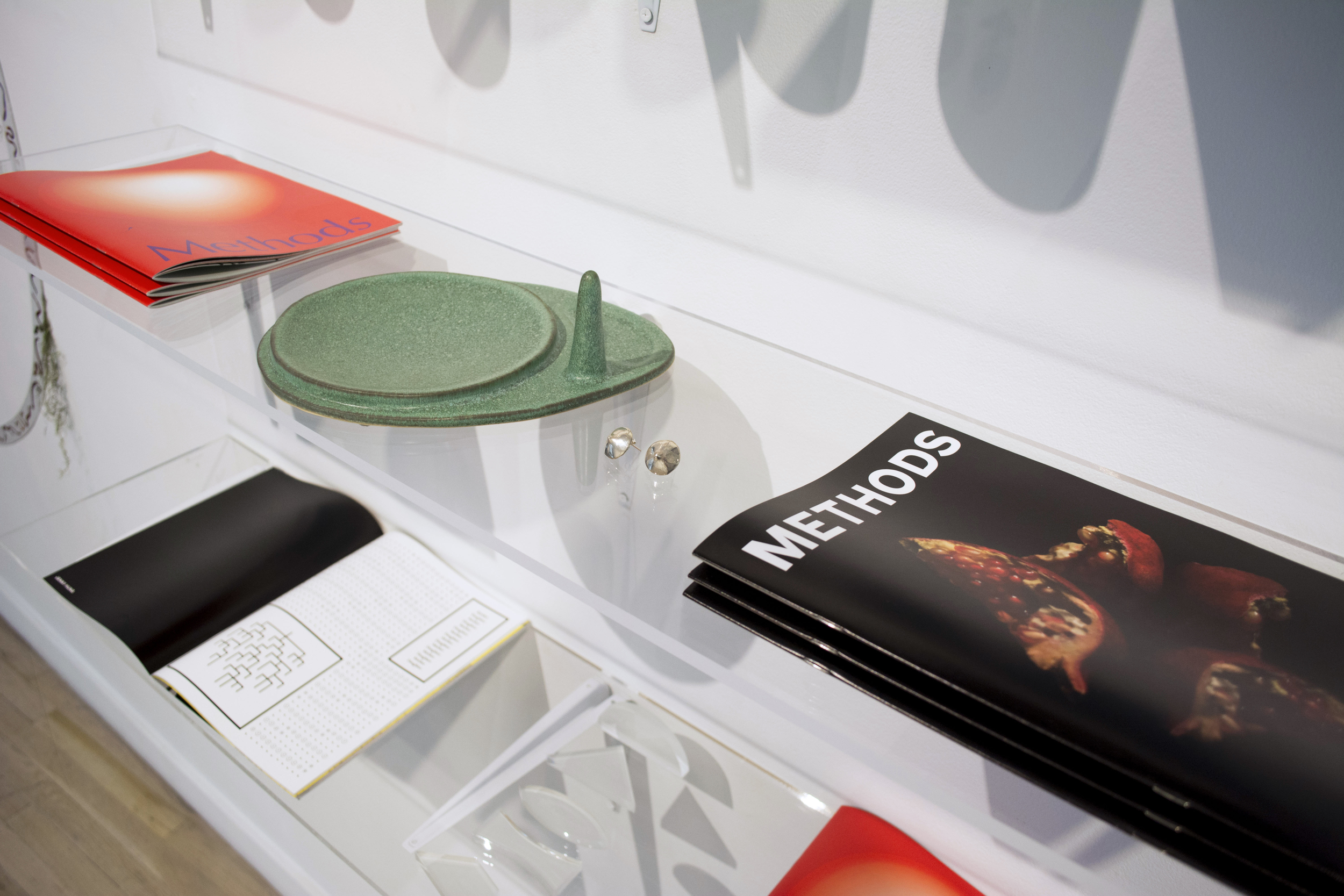 Ria Roberts  Design Within Reach , 2016  A shelving system composed of discarded plexiglass from exhibitions the Metropolitan Museum of Art, where Roberts works as a graphic designer, including (pictured) ceramics by Lauren Francescone, jewelry by Sarah Shikama,  Methods  magazine (No.1 and 2), and  Paid Vacation , 2016, a set of glass lens with Maslow's hierarchy of needs engraved on them by Ria Roberts.