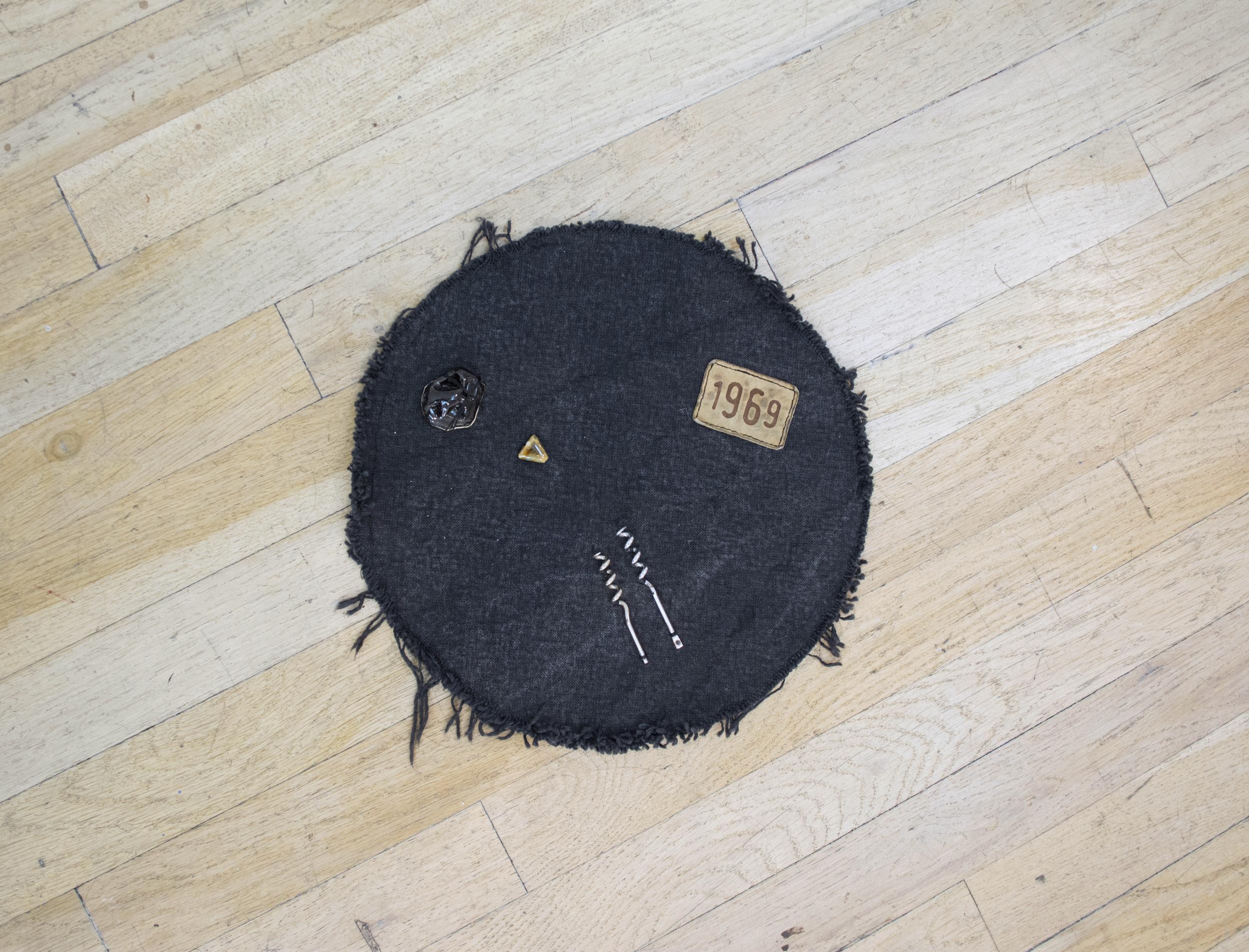 """Catherine Czacki   Post radical , 2016  Denim, black glazed ceramic, wine key elements, leather clothing tag, accompanied by text:  BB. 11.5"""" x 11.5"""" x 1"""""""
