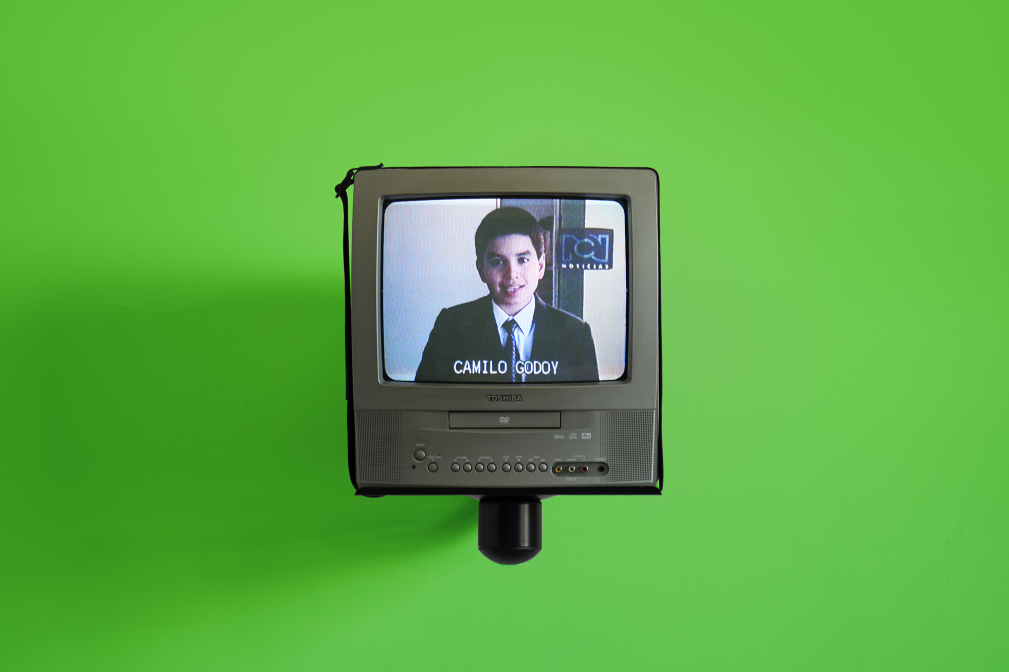 Camilo Godoy,  Noticiero  (installation view), 2002/2017. Video, sound, CRT television set, wall mount, chroma green screen wall, 10-minute loop.