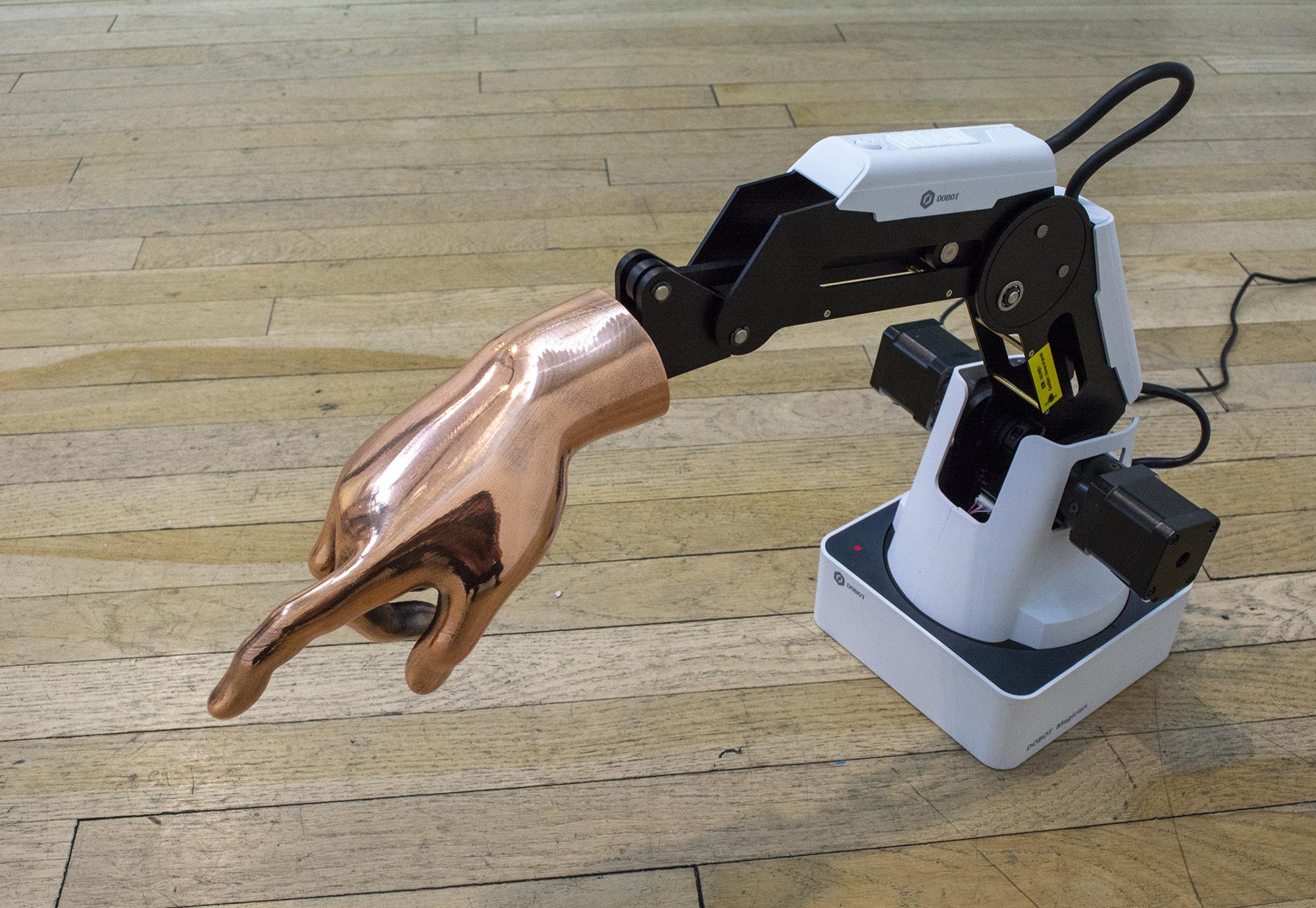Amanda Turner Pohan  ololyga, ololyzo, eleleu, elelizo, alala, alalazo, io!  2019 DoBot® Magician Robotic Arm, 3D printed and bronze electroplated hand of Calliope 24 x 10 x 14 inches