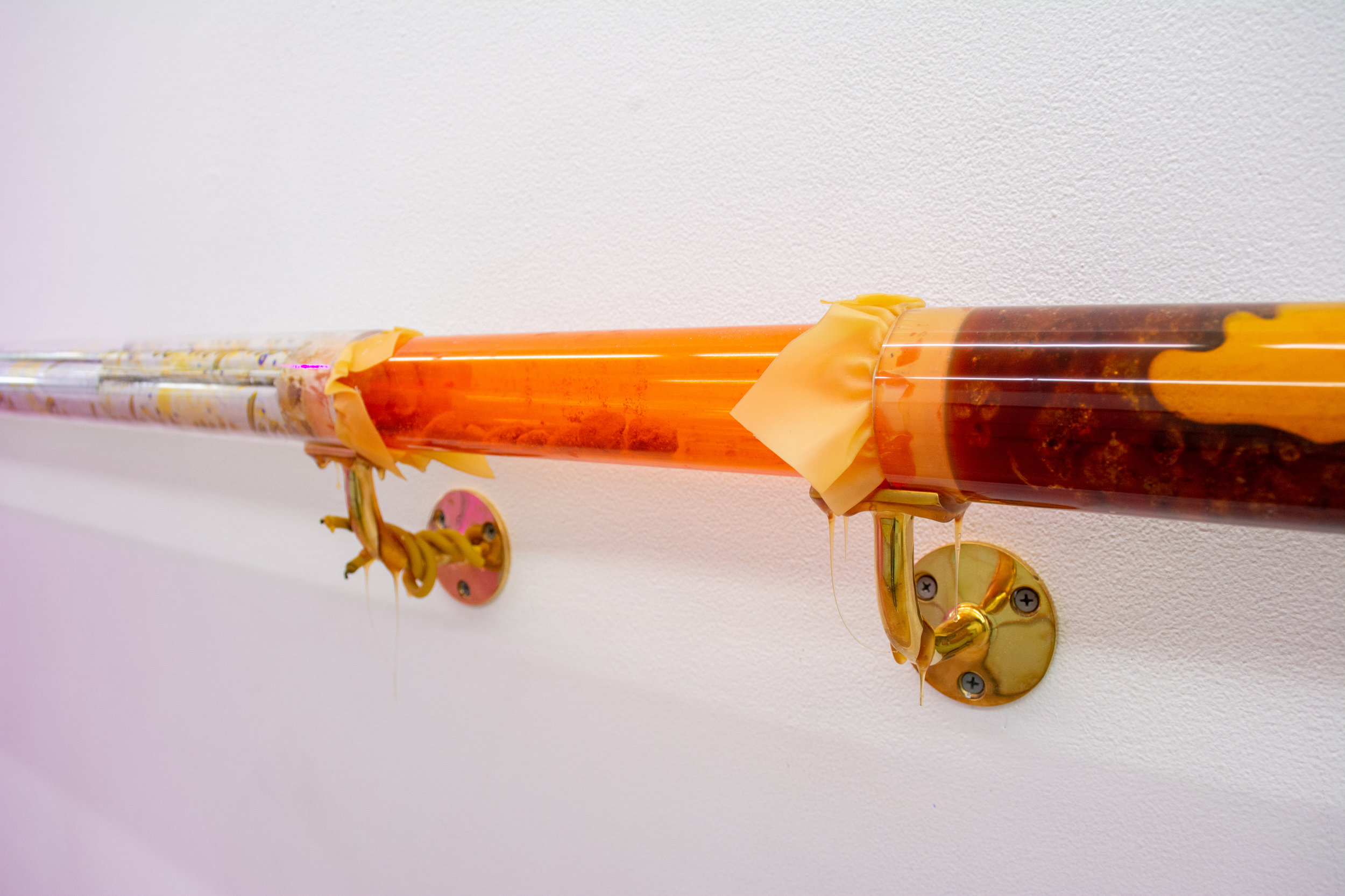 """Detail of  """"Dream"""" Guid  2018 Acrylic tubes, handrail brackets, hand blown glass, rubber, ceramic , honey, shredded government documents, pollen, beeswax, handmade lens, drawings 3 x 165 inches"""