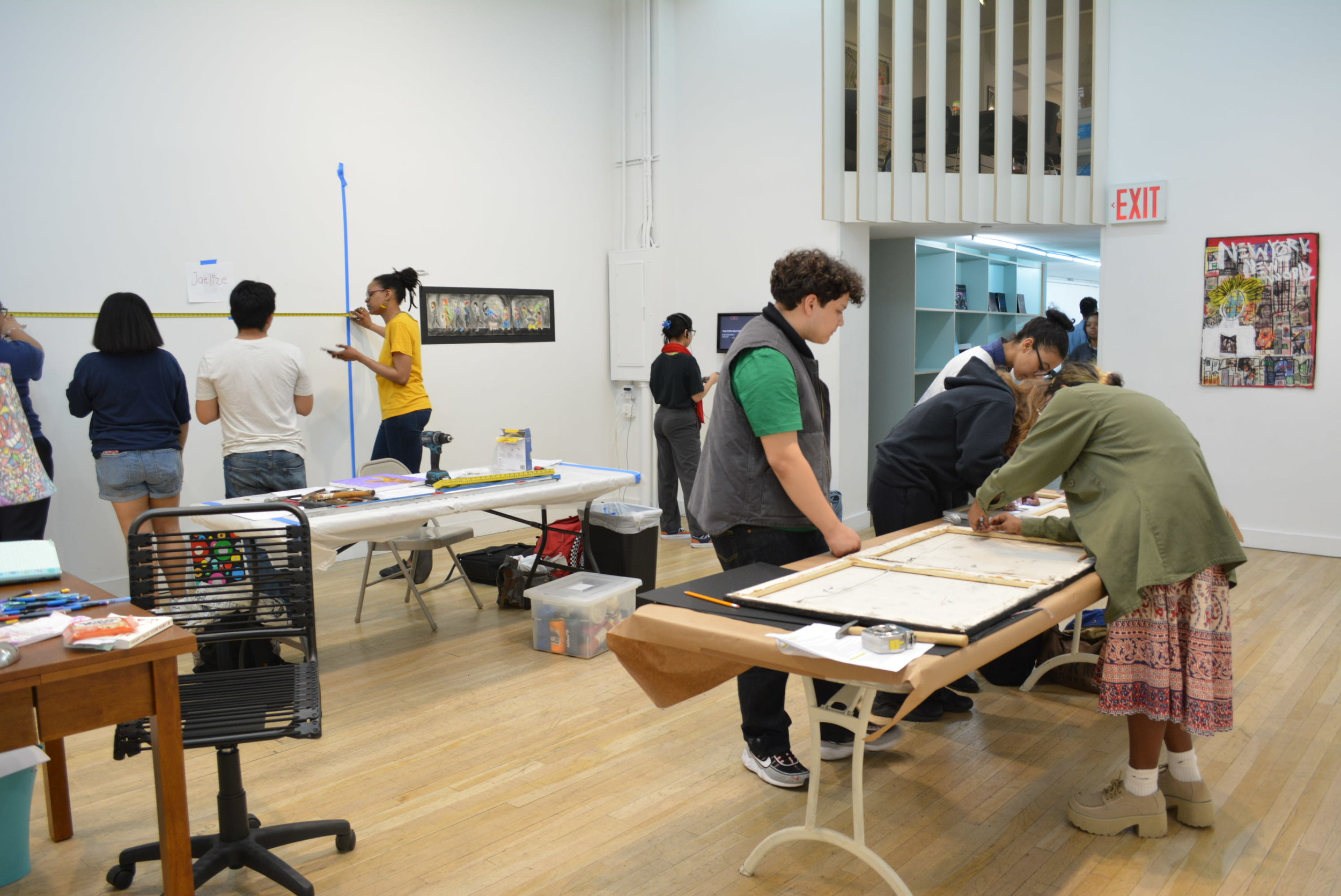Lead Educator Amanda Adams-Louis works with the CUE teens to install their final exhibition,  The Peristence of Memory.