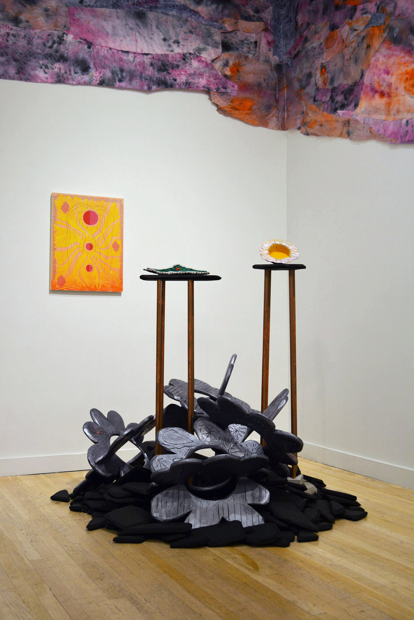 Installation view of Natessa Amin:  Hyphen .  [Image description: Installation view of the sculptures  Cooking Flower  and  Above Sea Level,  which sit on two metal pedestals. The pedestals are surrounded at the base by large, silver floral sculptures and a pile of charcoal-colored rubble made of foam. Behind the sculptures you can see Amin's wallpaper and the painting  I plunge my hands into the sun .]