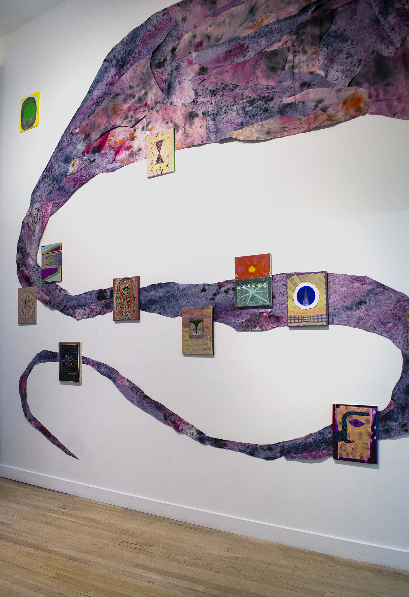 Installation view of Natessa Amin:  Hyphen .  [Image description: A long, undulating trail of purple hand-dyed newsprint curves across the wall. Hanging over it are ten 11 by 14-inch paintings decorated with large blocks of colors, web-like patterns, serpentine shapes, and evil eyes.]