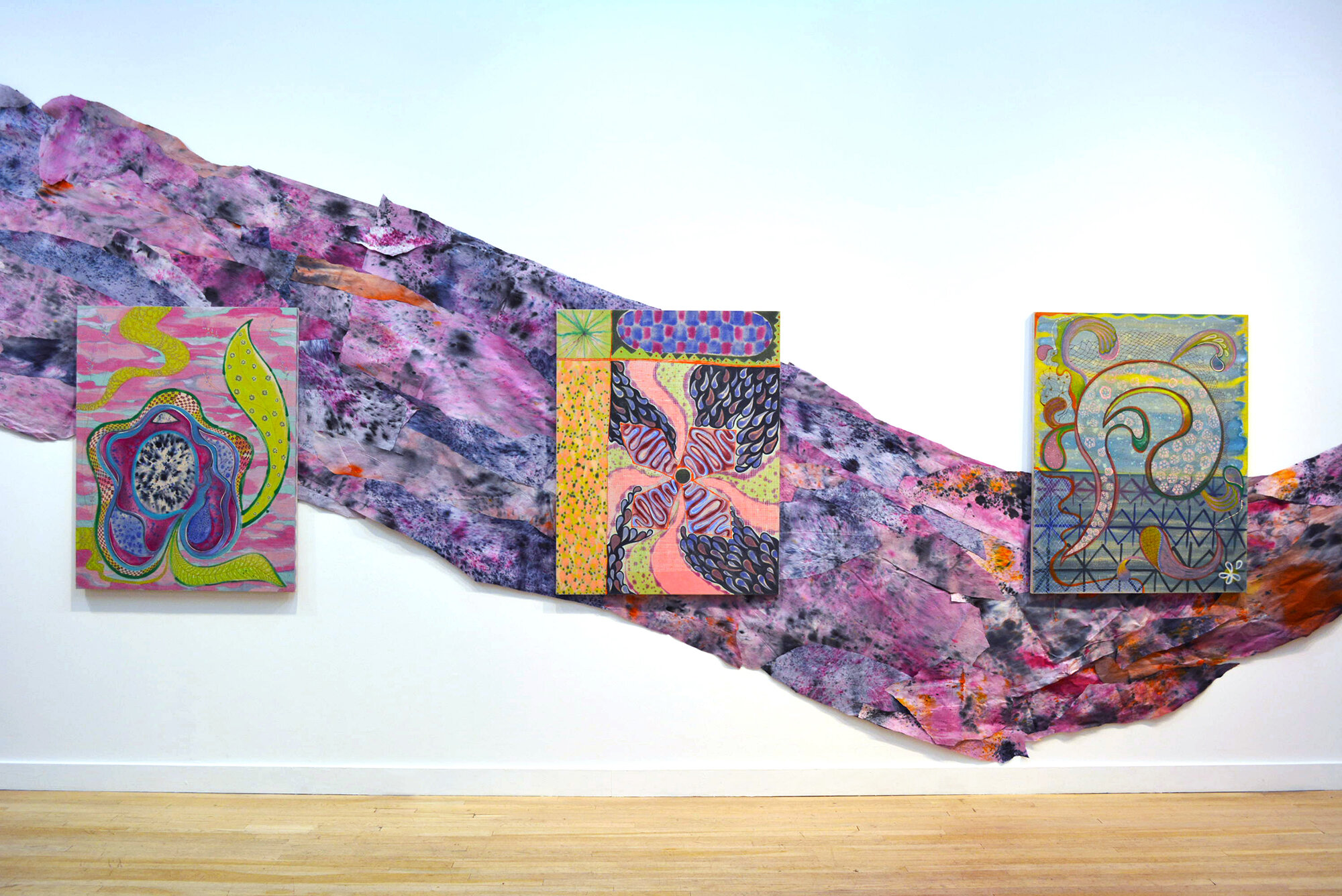 Installation view of Natessa Amin:  Hyphen .  [Image description: Installation view of three colorful patterned paintings, 36 by 46 inches each, hanging on top of purple, orange, pink, and blue hand-dyed and layered newsprint snaking across the wall of the gallery.]