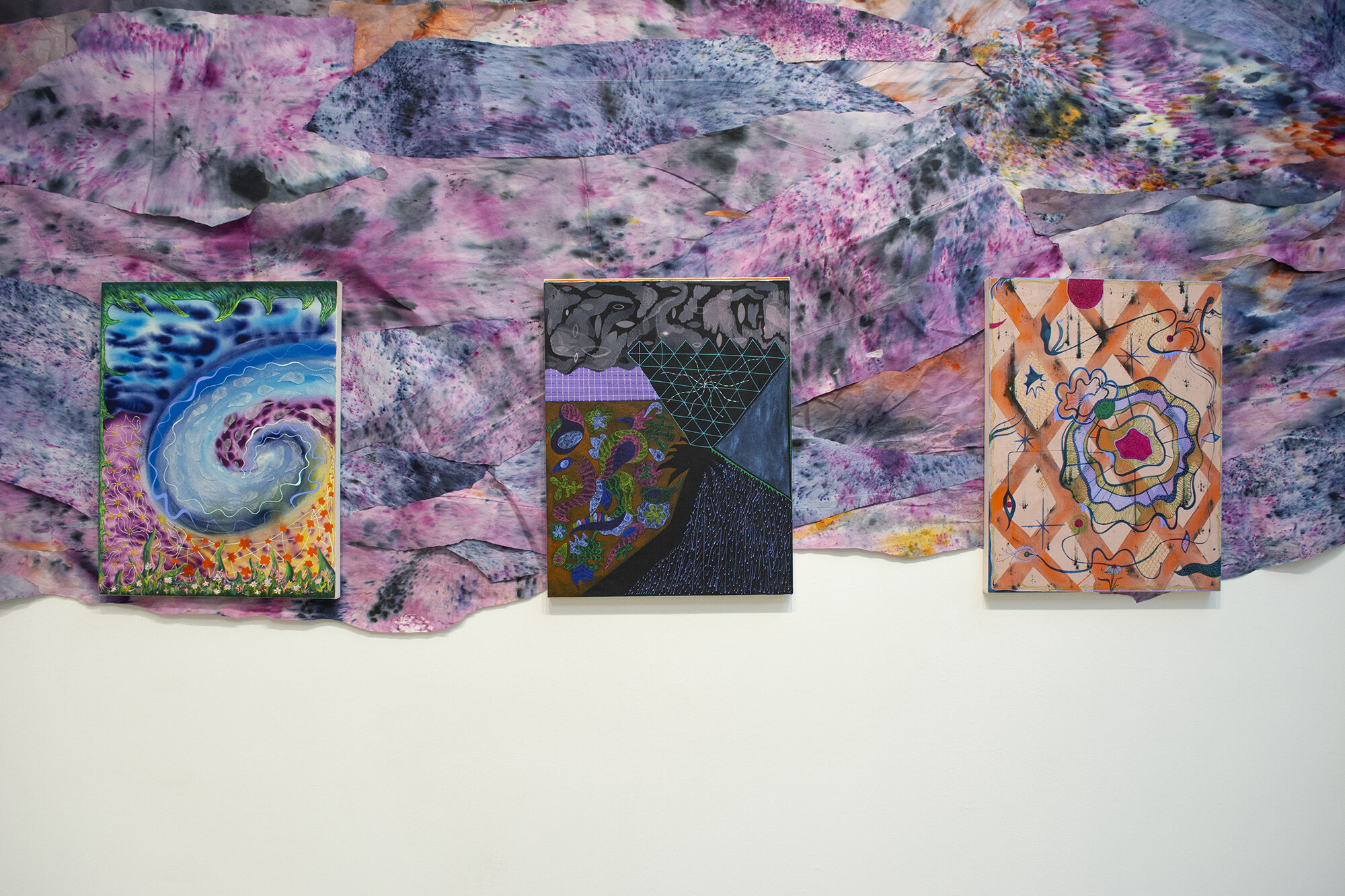 Installation view of Natessa Amin:  Hyphen .  [Image description: Installation view of three colorful patterned paintings, 20 by 26 inches each, hanging on top of purple, orange, pink, and blue hand-dyed and layered newsprint snaking across the wall of the gallery.]