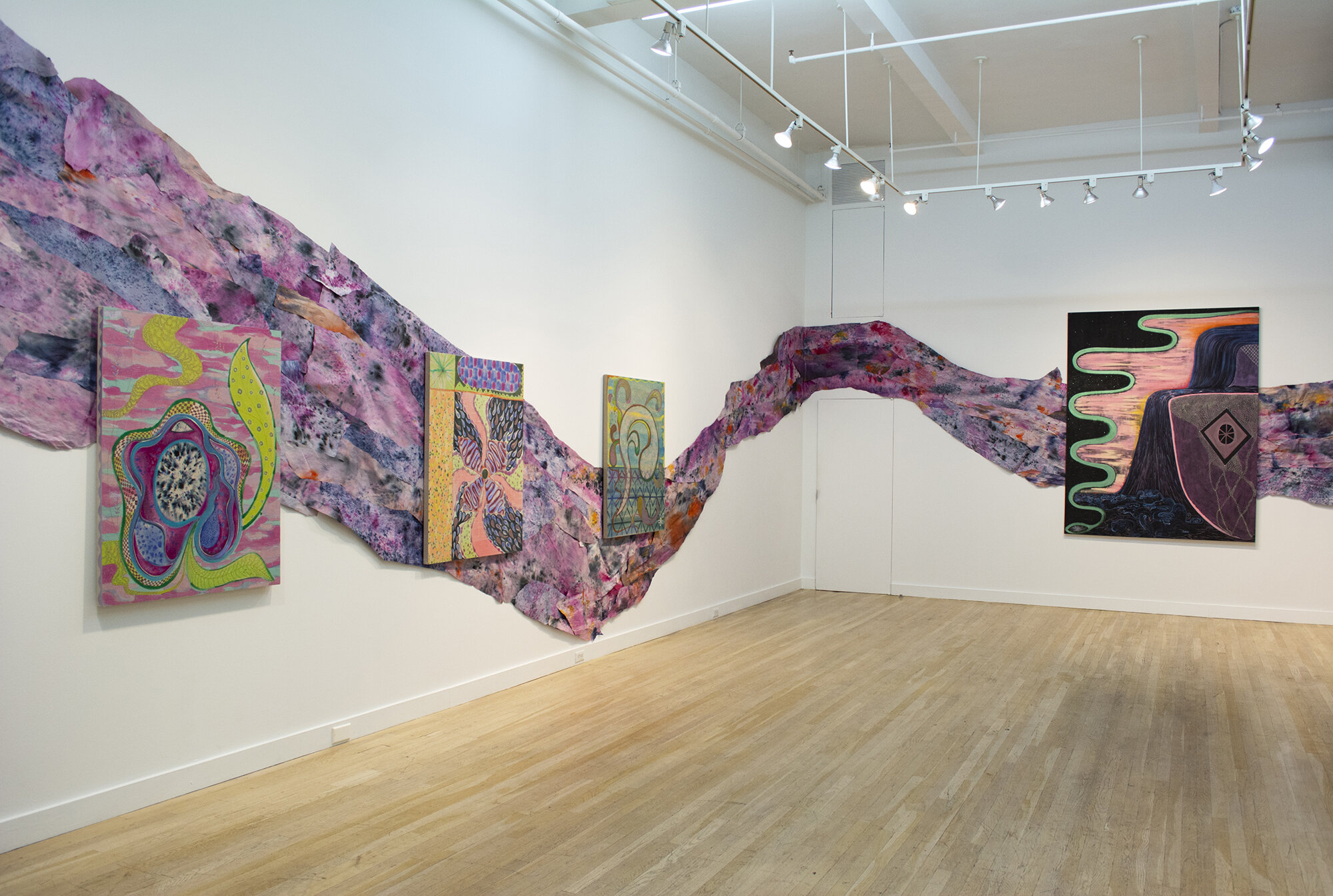 Installation view of Natessa Amin:  Hyphen .  [Image description: Installation view of two gallery walls with a curved strip of hand-dyed and layered newsprint, mostly pink in color with orange, red, purple, and gray hues mixed in throughout. On top of the newsprint is a row of three paintings on the left and one painting on the right.]