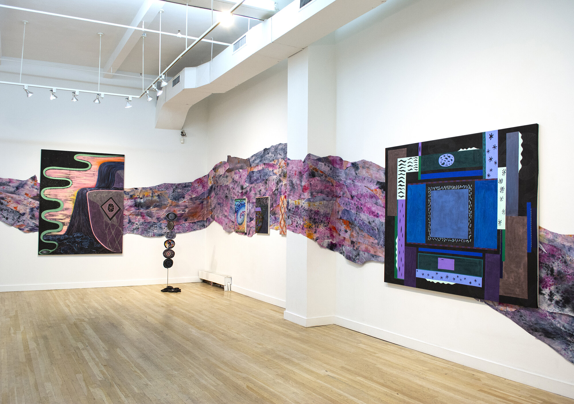 Installation view of Natessa Amin:  Hyphen .  [Image description: A long, undulating trail of purple, pink, and blue hand-dyed newsprint curves across the gallery walls. Hanging on top of it are two large and colorful paintings, approximately 5 by 7 feet each. In the corner of the room stands a black sculpture, 67 inches tall, of several round shapes stacked on top of one another.]