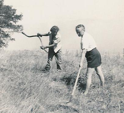 MEHER MOUNT RELIES ON VOLUNTEERS to help with weed abatement and general maintenance. Agnes Baron (left) is using a scythe and visitor Margaret Craske, a close disciple of Meher Baba (right), helps by raking circa 1949. (Archive photo.)