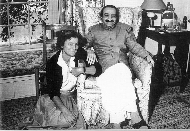AVATAR MEHER BABA (seated) when He visited Meher Mount on August 2, 1956. This photo is taken with caretaker Agnes Baron beside Him. They are in the guesthouse where Meher Baba met with His followers that day. This building was completely destroyed in the 1985 New Life Fire. (Archive photo.)