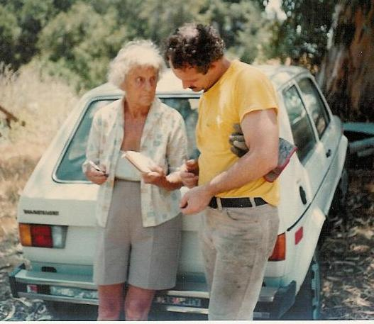 """AGNES BARON writing instructions to Sam Ervin during a Silence Day """"Work Party"""" at Meher Mount in the late 1970s. (Margaret Magnus photo.)"""