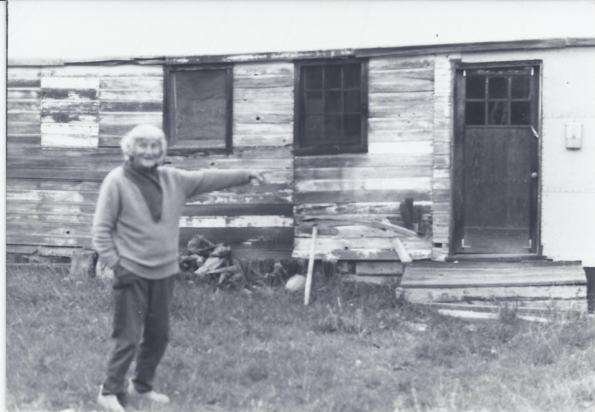 """AGNES BARON pointing to the carpenter's shed, also known as """"the white house,"""" where the  mandali  were to stay for the planned 10-day visit to Meher Mount in 1952."""
