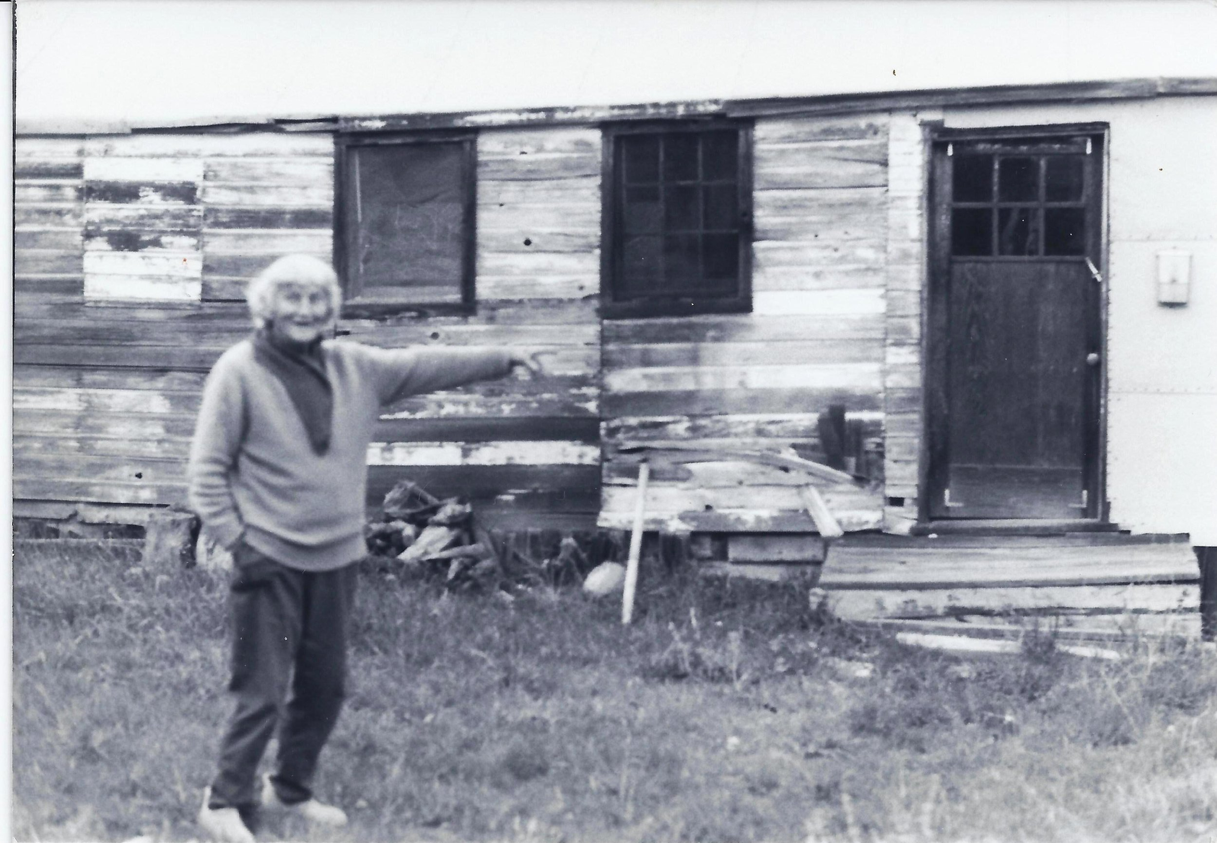 """AGNES BARON in the early 1980s pointing to the """"white house,"""" the army carpenter's shed brought onto the property to house Meher Baba's  mandali  (close disciples) for His planned 1952 visit to Meher Mount. Agnes (1907-1994) was a co-founder and lifetime caretaker for Meher Mount."""