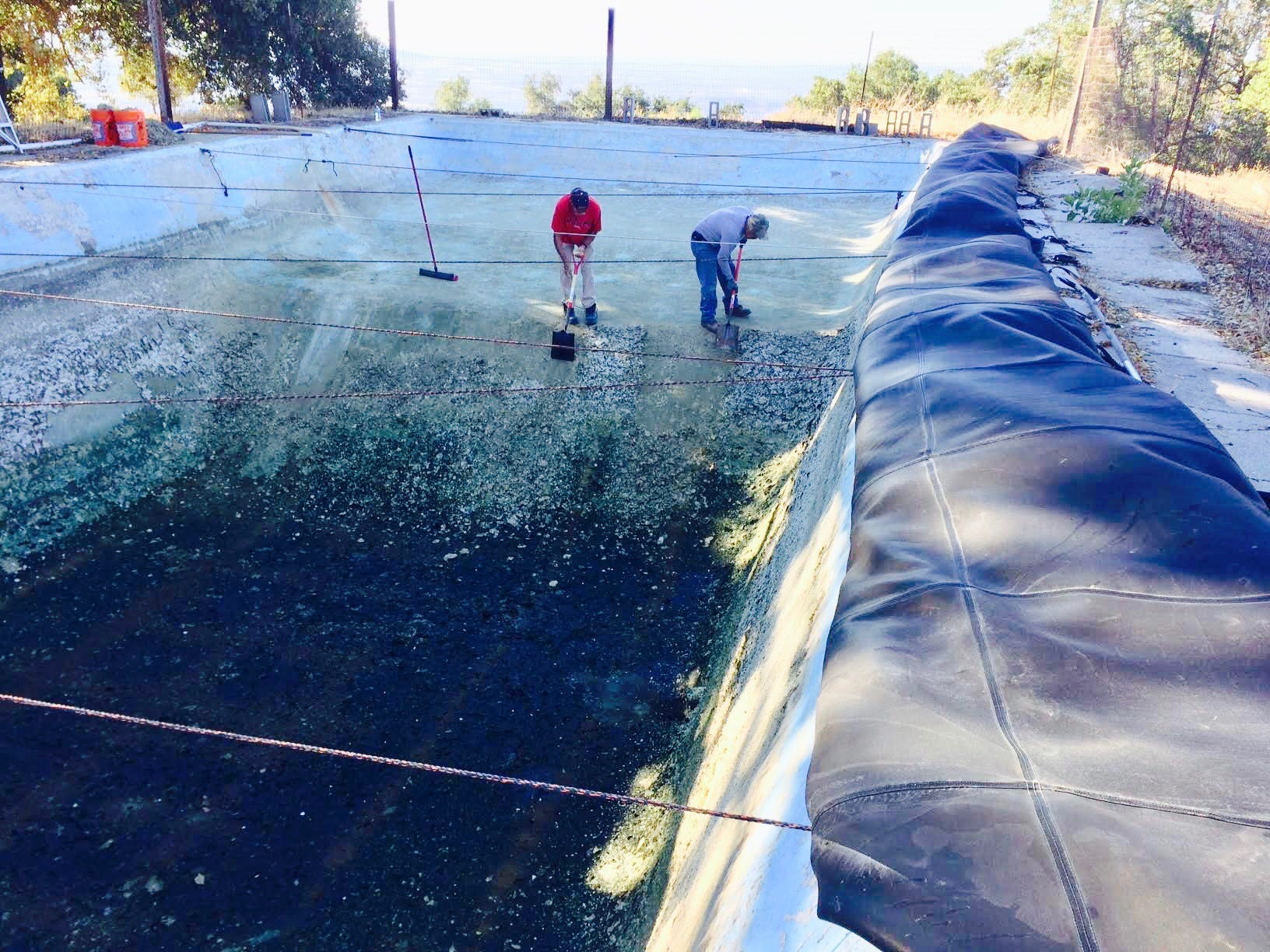 CLEANING THE SWIMMING POOL at Meher Mount of accumulated bio-matter. The pool acts as a reservoir for water pumped from the well. From here, the water goes through a treatment system before going to the Visitor Center/Caretaker Quarters. (Photo: Buzz Glasky, 2016)