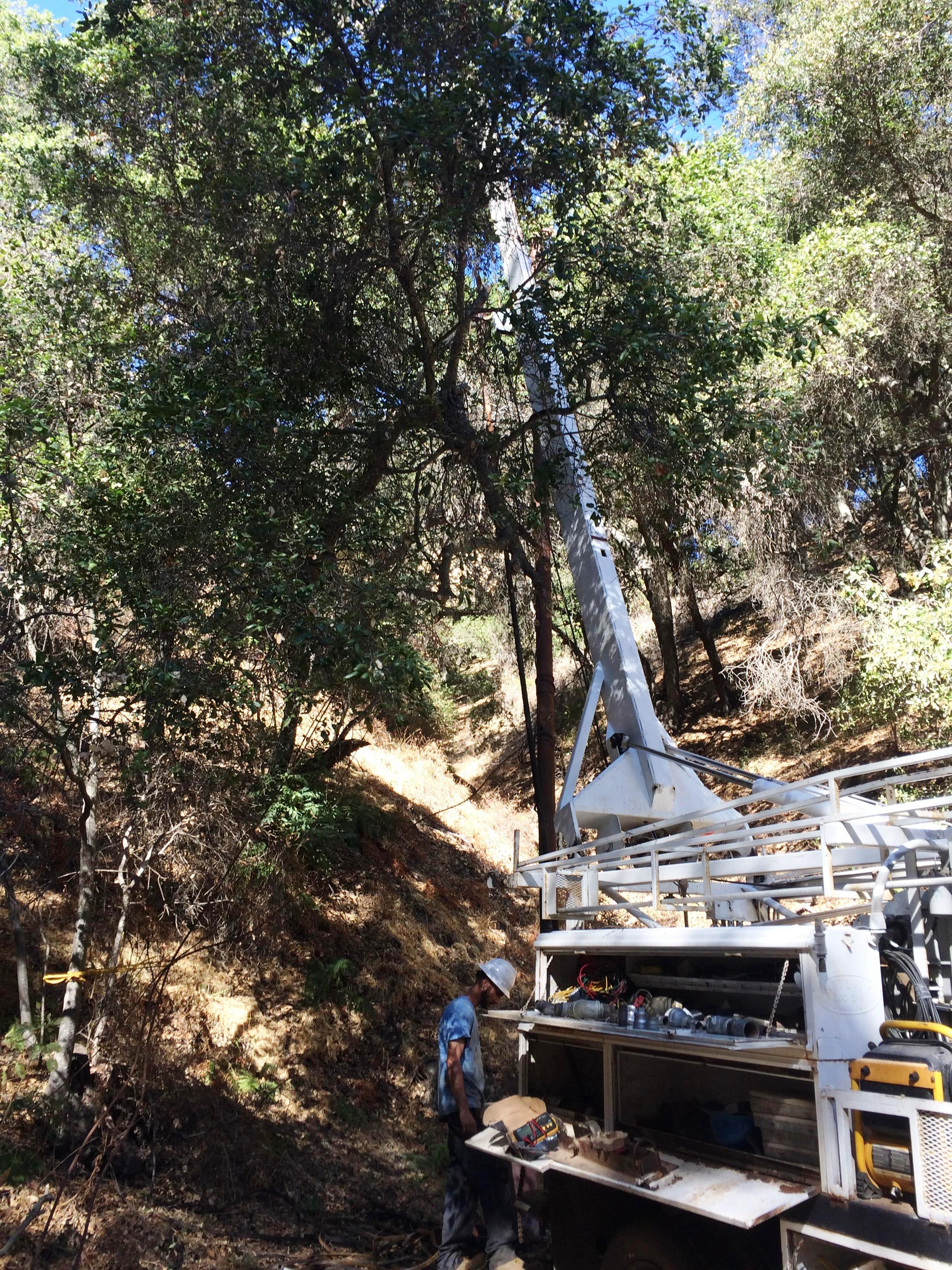 HANSEN WELL-DO SERVICE assessing the well and pump situation at the well head located in a ravine at Meher Mount. (Photo: Buzz Glasky, 2016)