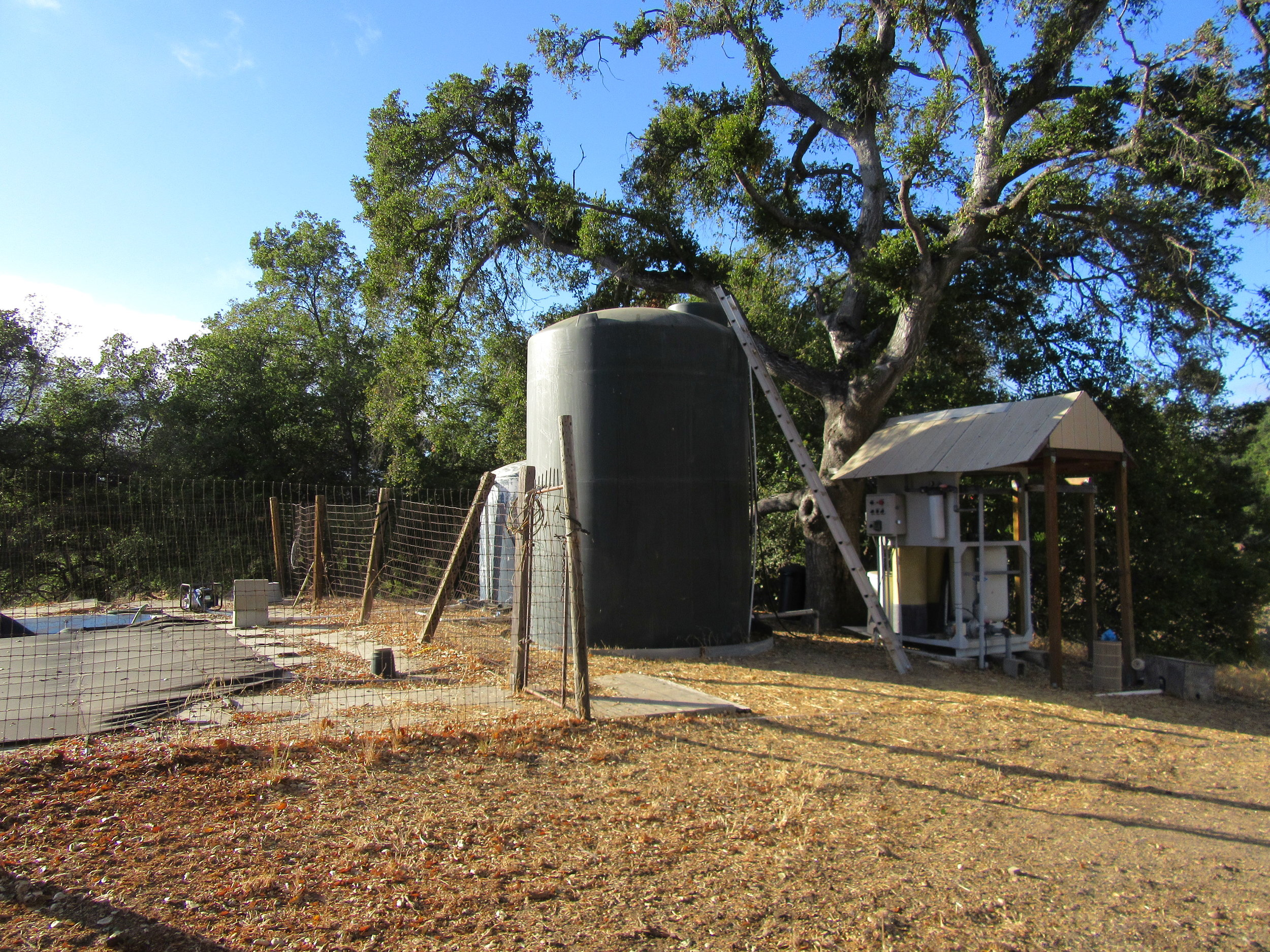 WATER TREATMENT SYSTEM - The former swimming pool, which acts as a reservoir for the water pumped from the well, is to the left enclosed by fencing. The large holding tank in front is for treated water. The smaller holding tank in back is for untreated agricultural water. The water treatment system is to the right. (Photo: Sam Ervin, 2016)
