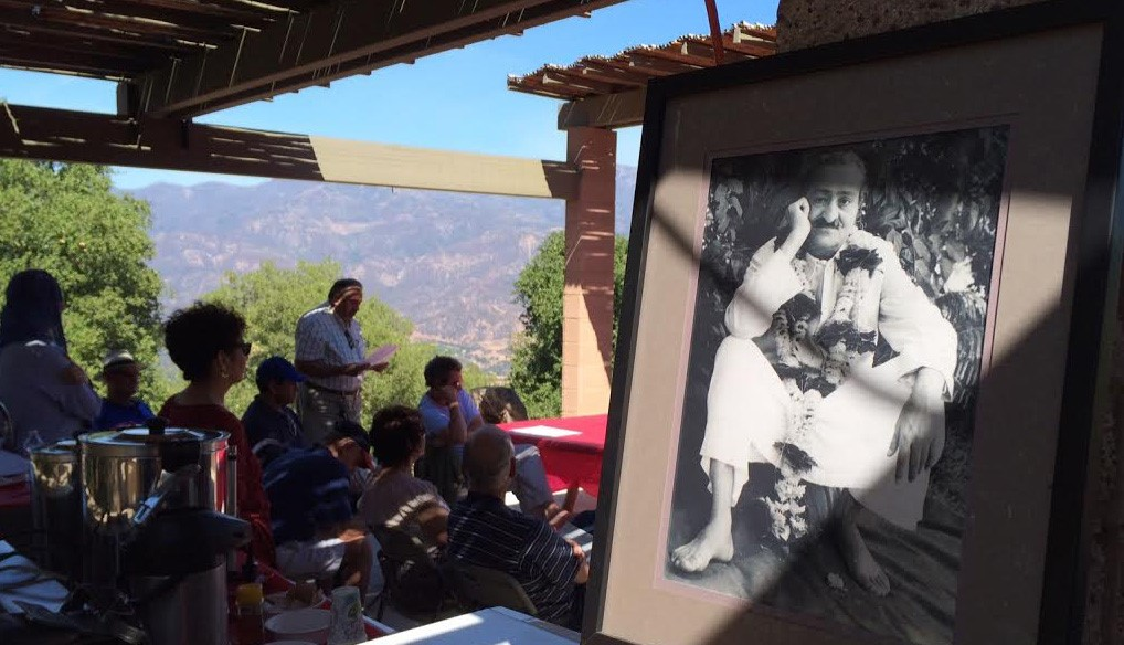 READING FROM  Lord Meher  at the  Gutta  Breakfast with a photo of Avatar Meher Baba in the foreground. (Photo: Buzz Glasky, 2014).