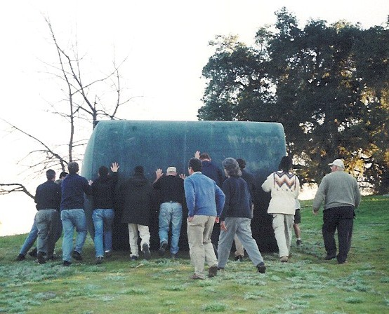MANY HANDS MAKE LIGHT WORK. When the then new water system was being installed in 2004, a group of volunteers joined together to roll the water tank up the hill to sit beside the pool. Because so many joined the effort, it was almost effortless. (Photo: Sam Ervin)
