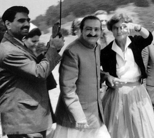 AVATAR MEHER BABA at Meher Mount on August 2, 1956. Close disciple Eruch Jessawalla is holding the umbrella and Meher Mount caretaker Agnes Baron is pointing out something to Meher Baba.