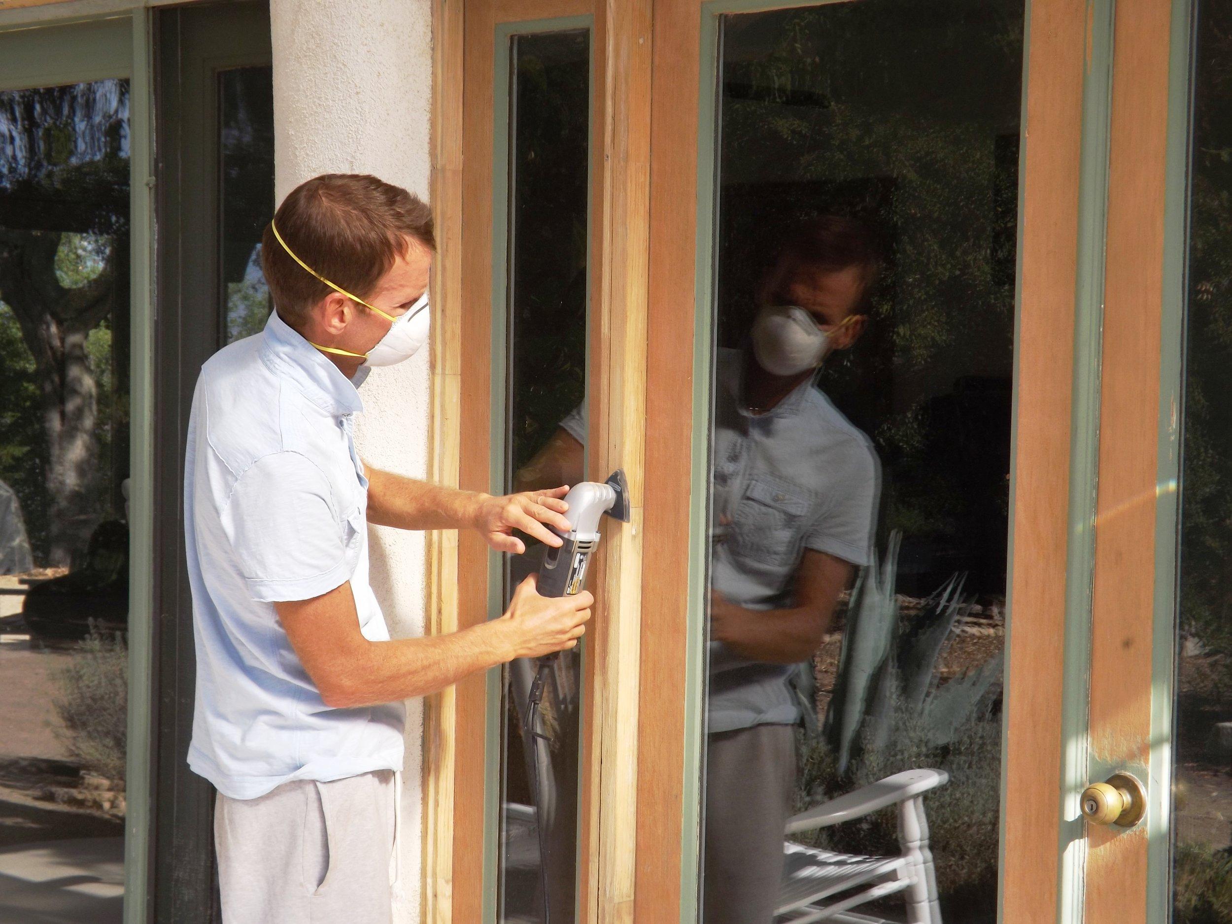 LESLIE BRIDGER sanding the door and window frames in preparation for painting them. (Photo: Rebecca Bridger, 2012)