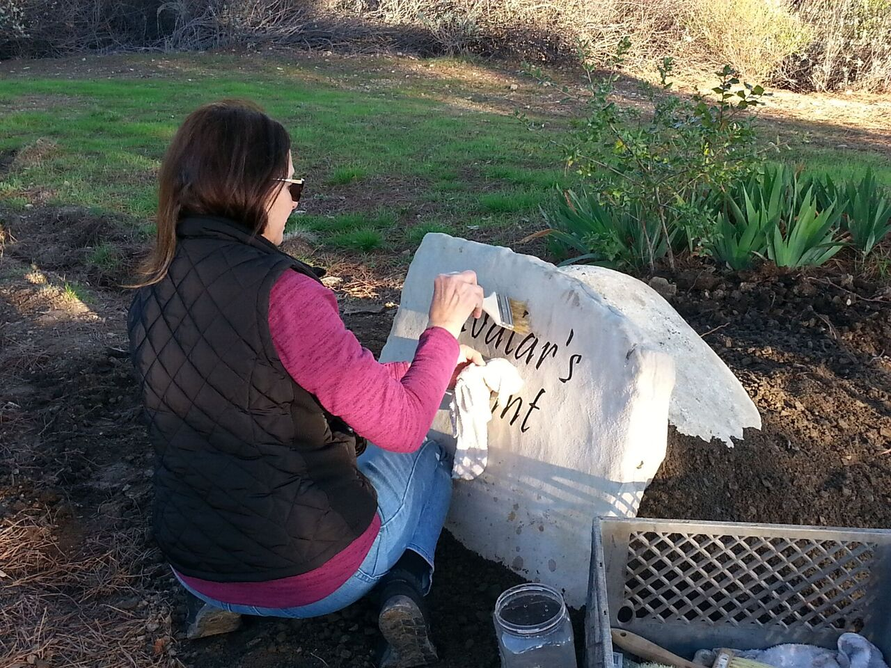 DIANE CONOVER of Stonehenge Signs, Inc. dusting off all the signs, including this one for Avatar's Point.(Photo: Margaret Magnus, January 2017)