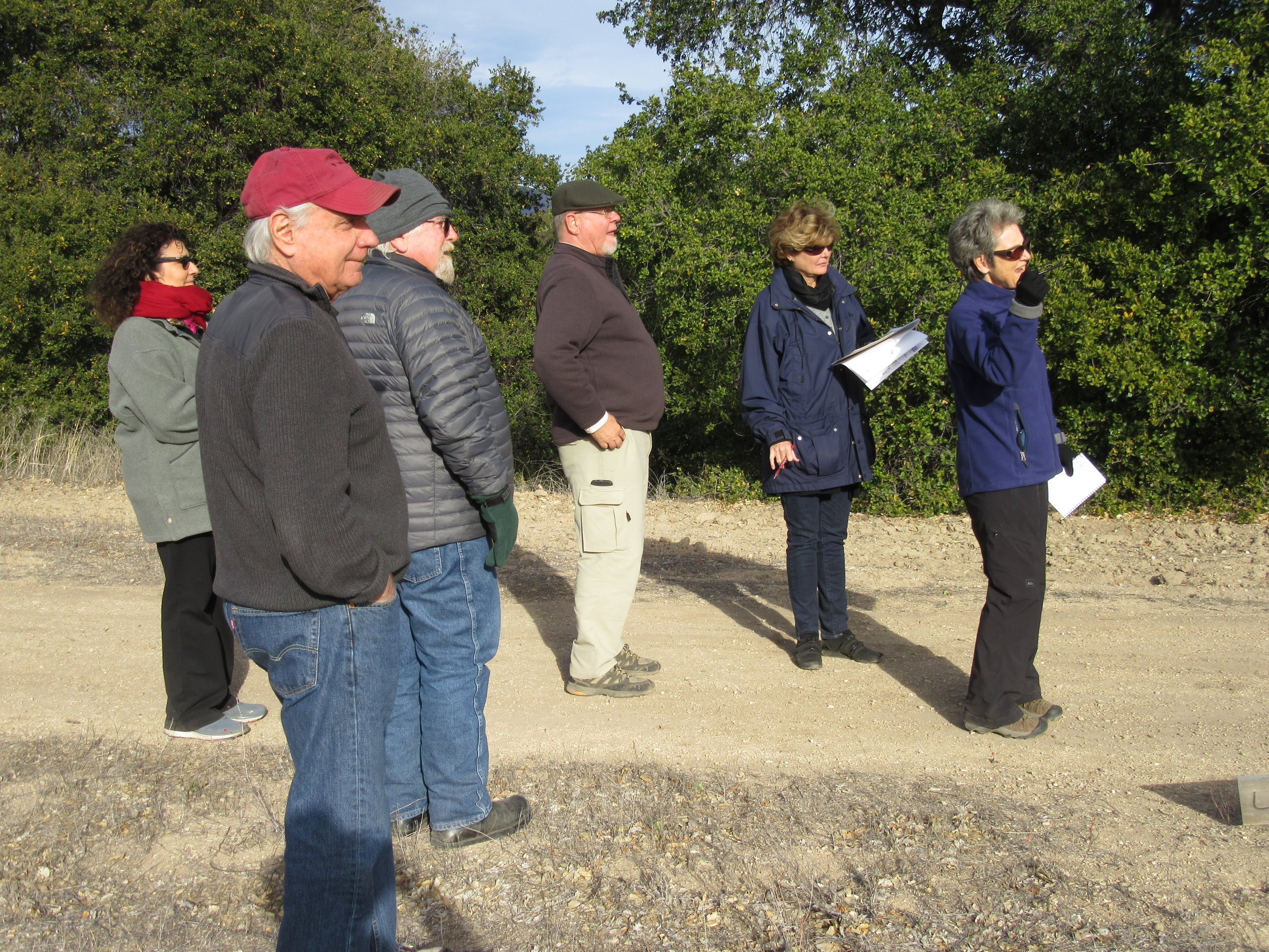 MEMBERS OF THE SIGN COMMITTEE walk the property to discuss the signage options. (Left to right): Marta Flores, sign advocate; Jim Whitson, board member;Buzz Glasky, manager/caretaker; Bryon Pinckert, architect volunteer; Nancy Pinckert, graphic desinger; and Margaret Magnus, communications director. (Photo: Sam Ervin, January 2016)
