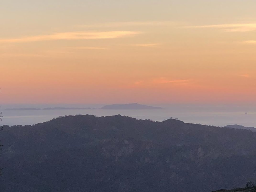 A SUNSET over the Pacific Ocean as seen from Avatar's Point and Baba's Tree marks the conclusion of a very successful workday at Meher Mount. (Photo: Bing Heckman, January 28, 2010)