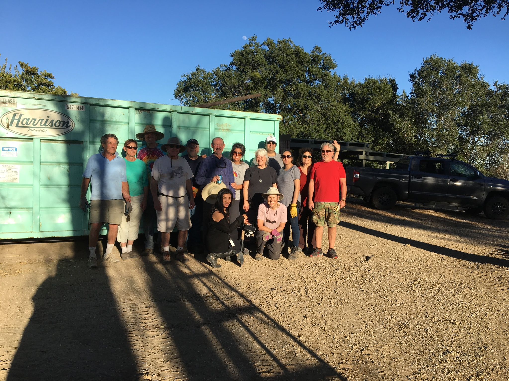 AT DAY'S END by the now-full dumpster. (Left to right) Jim Auster, Merrliee Bliss, James Whedon, James Whitson, Buzz Glasky, Sam L. Ervin, Yolanda Koumidou, Ginger Glasky, Homayar Gandhi, Khushnam Crawford, Marta Flores, Satya Keyes. (Kneeling) Sarah Larsen, Margaret Magnus. (In shadow) Bing Heckman. (Photo: Cassandra Bramucci, January 28, 2018)