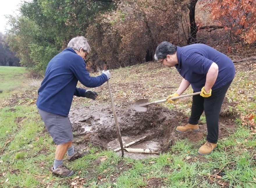 KYLE MORRISON AND HOMAYAR GANDHI digging to find the source of the leak - a broken pipe. But why did it start now, after all these years? (Photo: Margaret Magnus, March 11, 2018)