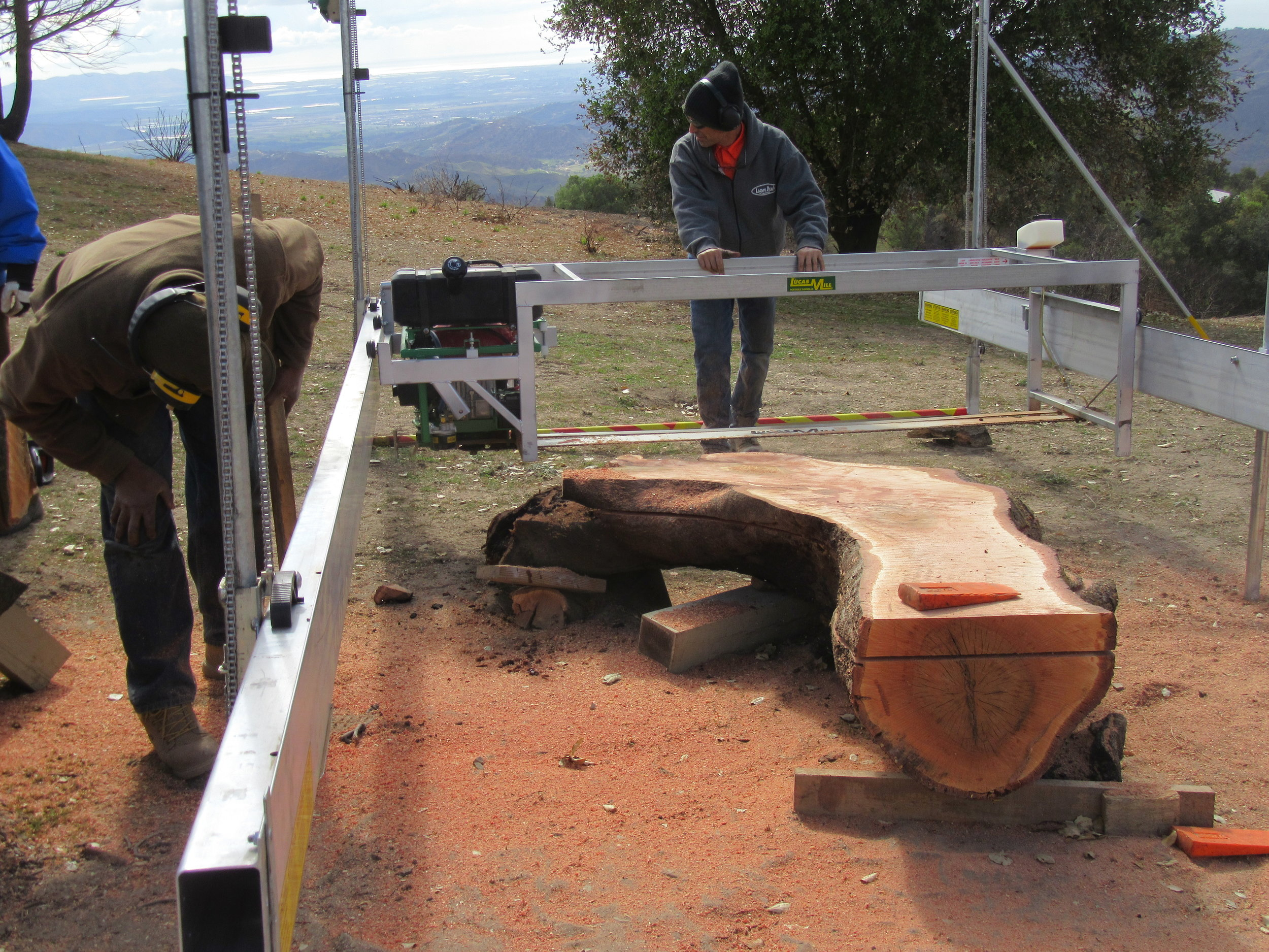 HAROLD GREENE (left) assessing the milling process of one the large limbs that would become an outdoor bench at Meher Mount. The top section was milled into planks, and the bottom section used for a bench. Peter Harnisch (center) is doing the actual milling with his portable saw on site at Meher Mount on February 13, 2018. (Photo: Sam Ervin)