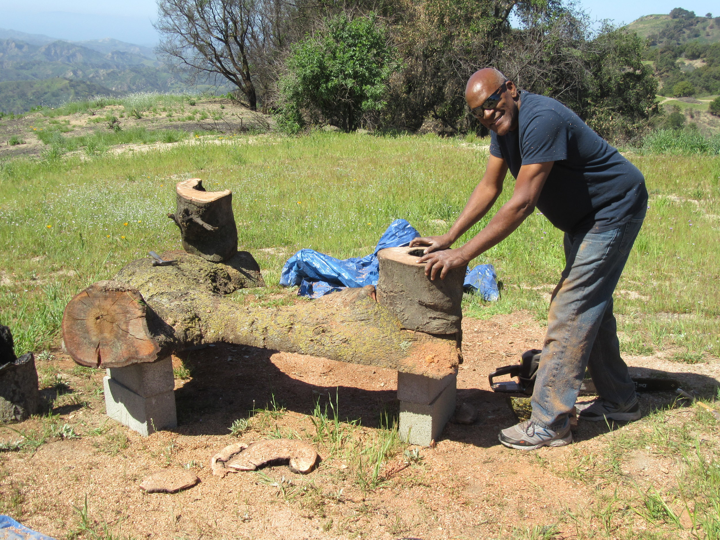 ARTISAN HAROLD GREENE fitting and attaching the legs onto one of the benches made from the fallen limbs of Baba's Tree at Meher Mount. (Photo: Sam Ervin, April 20, 2018)