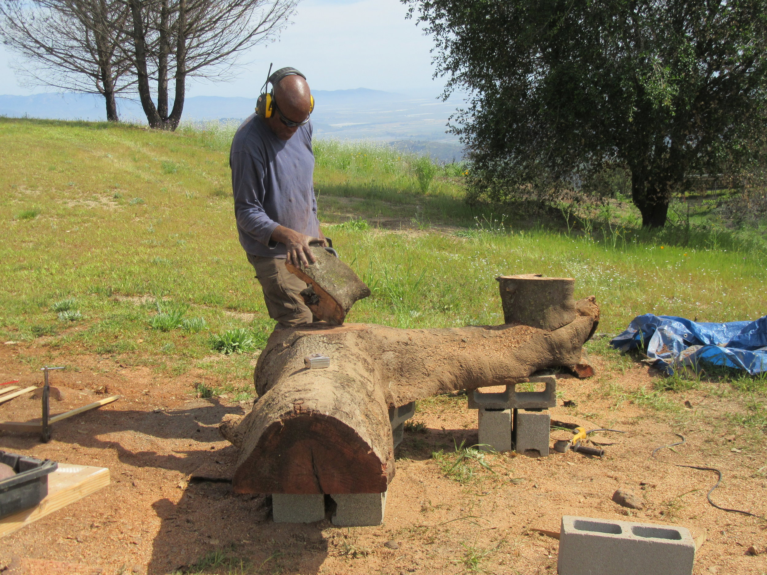 ARTISAN HAROLD GREENE attaching the legs - made of burned wood from Baba's Tree - to the half logs that were milled specifically to be used as outdoor benches at Meher Mount. (Photo: Margaret Magnus, April 21, 2018)