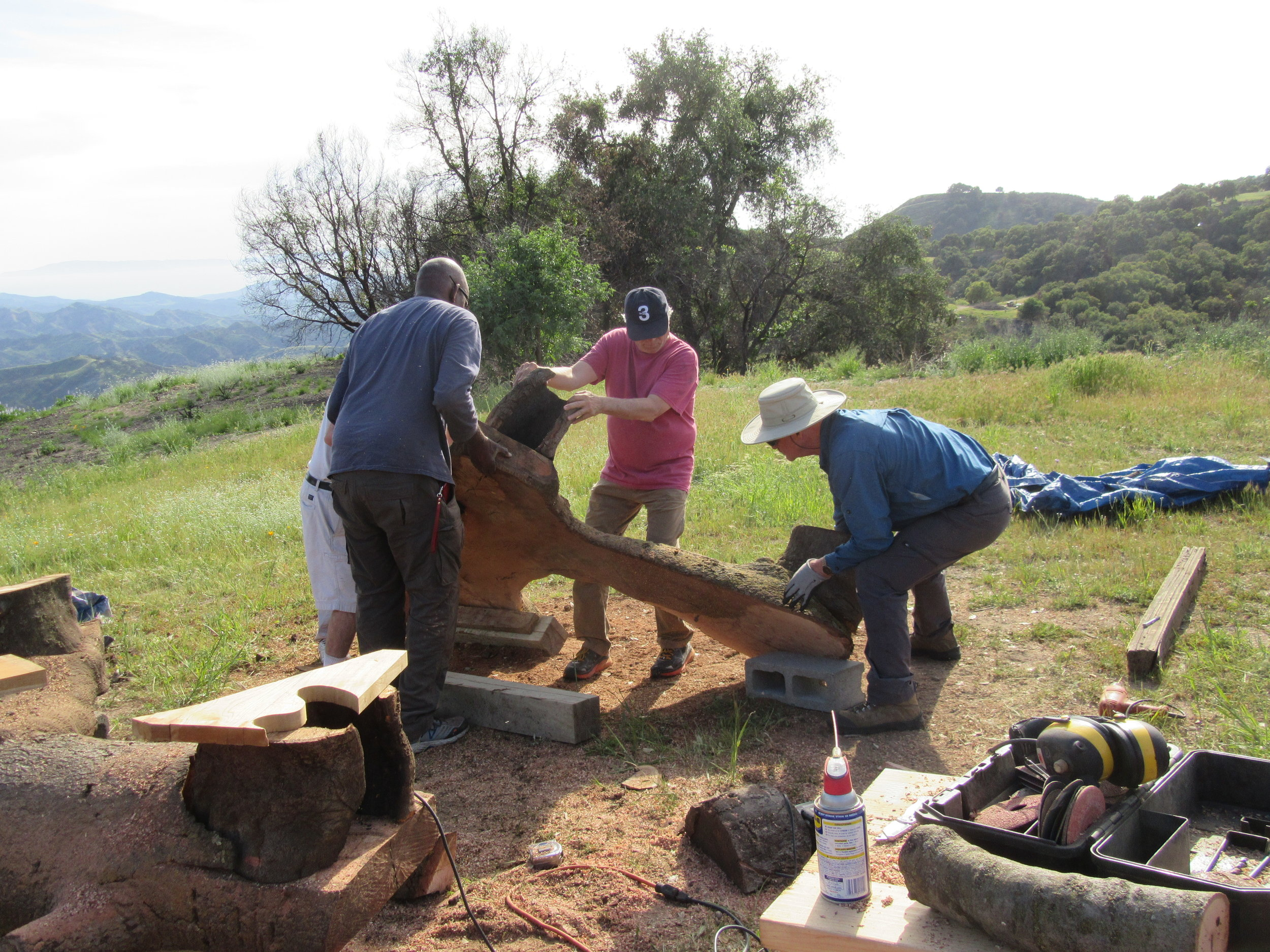 TURNING THE HALF LOGS after the legs have been attached takes four people -artisan Harold Greene and Meher Mount board members Jim Whitson, Robert Turnage and Sam L. Ervin. (Photo: Margaret Magnus, April 21, 2018)