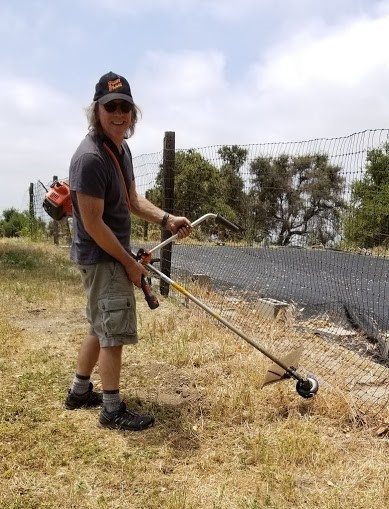 BRAD SPURR used the weed wacker around the pool and water treatment system. (Photo: Margaret Magnus, May 19, 2018)