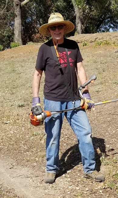 JIM WHEDON with a gas-powered weed wacker to reach difficult places. (Photo: Margaret Magnus, May 19, 2018)