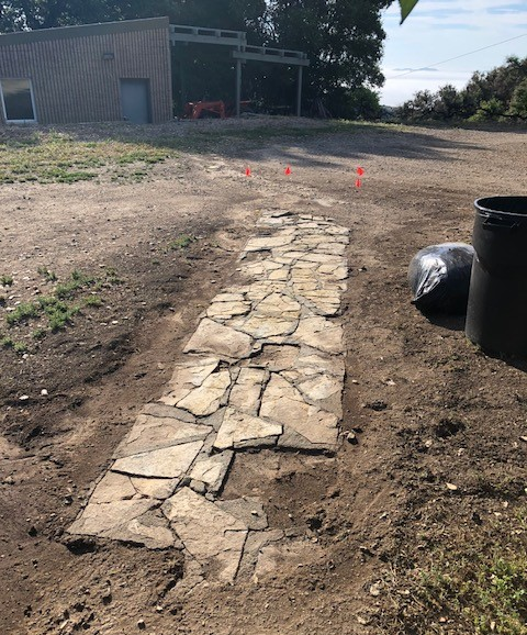 WEED ABATEMENT work draws attention once again to Baba's Walkway at Meher Mount. Eric Turk began excavation work to uncover eight feet of the sandstone path. (Photo: Cassandra Bramucci, May 2018)