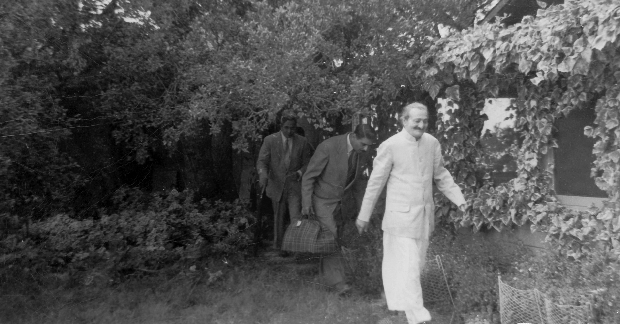 AVATAR MEHER BABA walking from the guesthouse at Meher Mount on August 2, 1956. On His left is screened porch of the main house, He is followed by Eruch Jessawala and Meherjee Karkaria. (Photo: (c) Meher Nazar Publications)