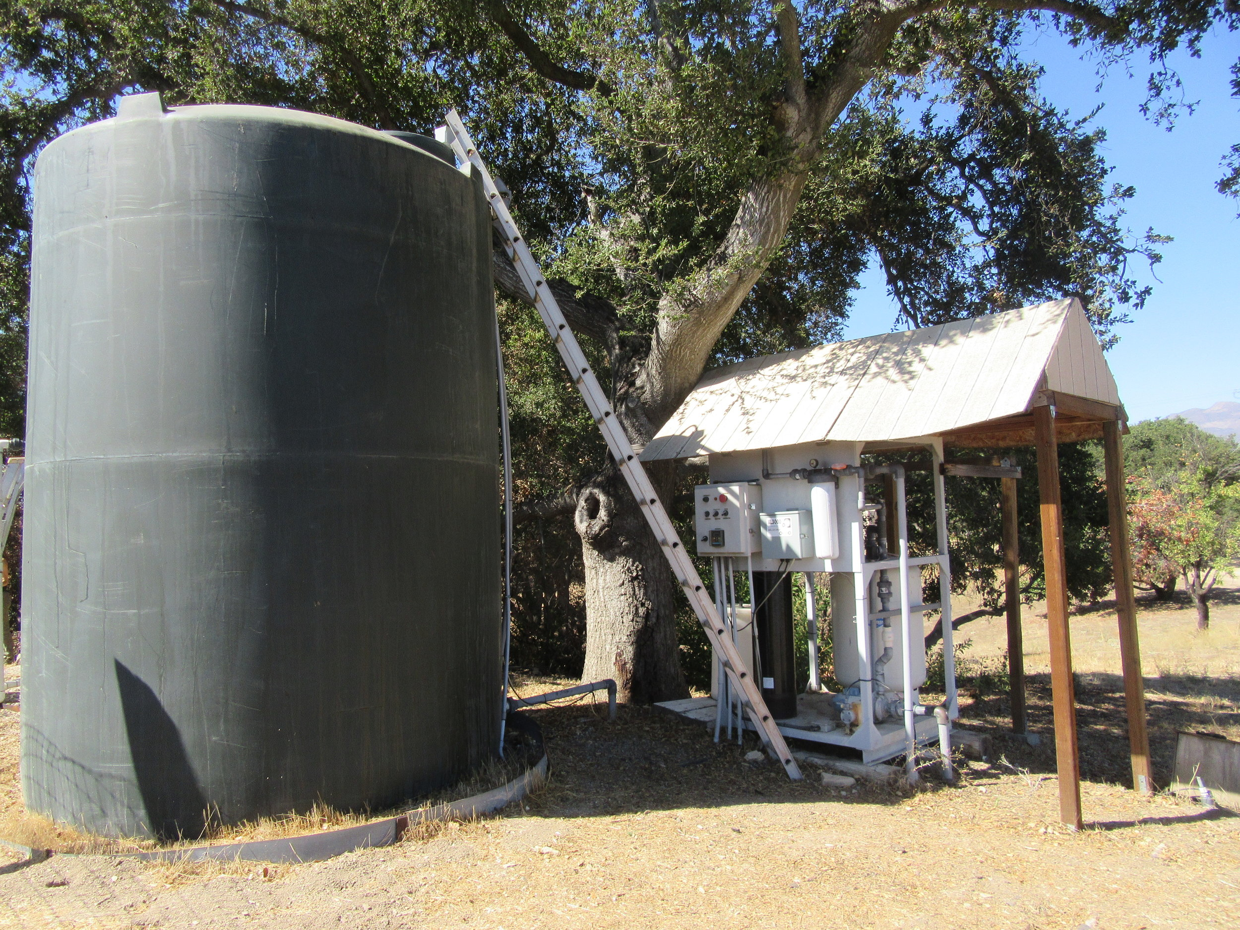 """ONE OF TWO WATER TANKS next to the upgraded water treatment system for Meher Mount's well water. This large tank holds potable water, while a smaller """"ag tank"""" holds untreated water for watering plants at the Visitor Center and Baba's Tree. (Photo: Margaret Magnus, September 2018)"""