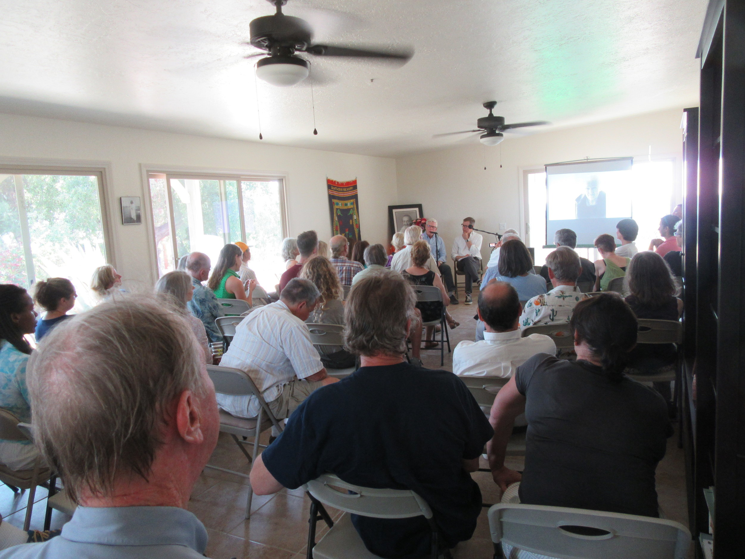 THE 2018 CELEBRATION of the anniversary of Avatar Meher Baba's visit to Meher Mount after removing the indoor fireplace. Special guests Charles Haynes and Christopher Wilson are seated in the area formerly occupied by the stove. (Photo: Sam Ervin, August 4, 2018)
