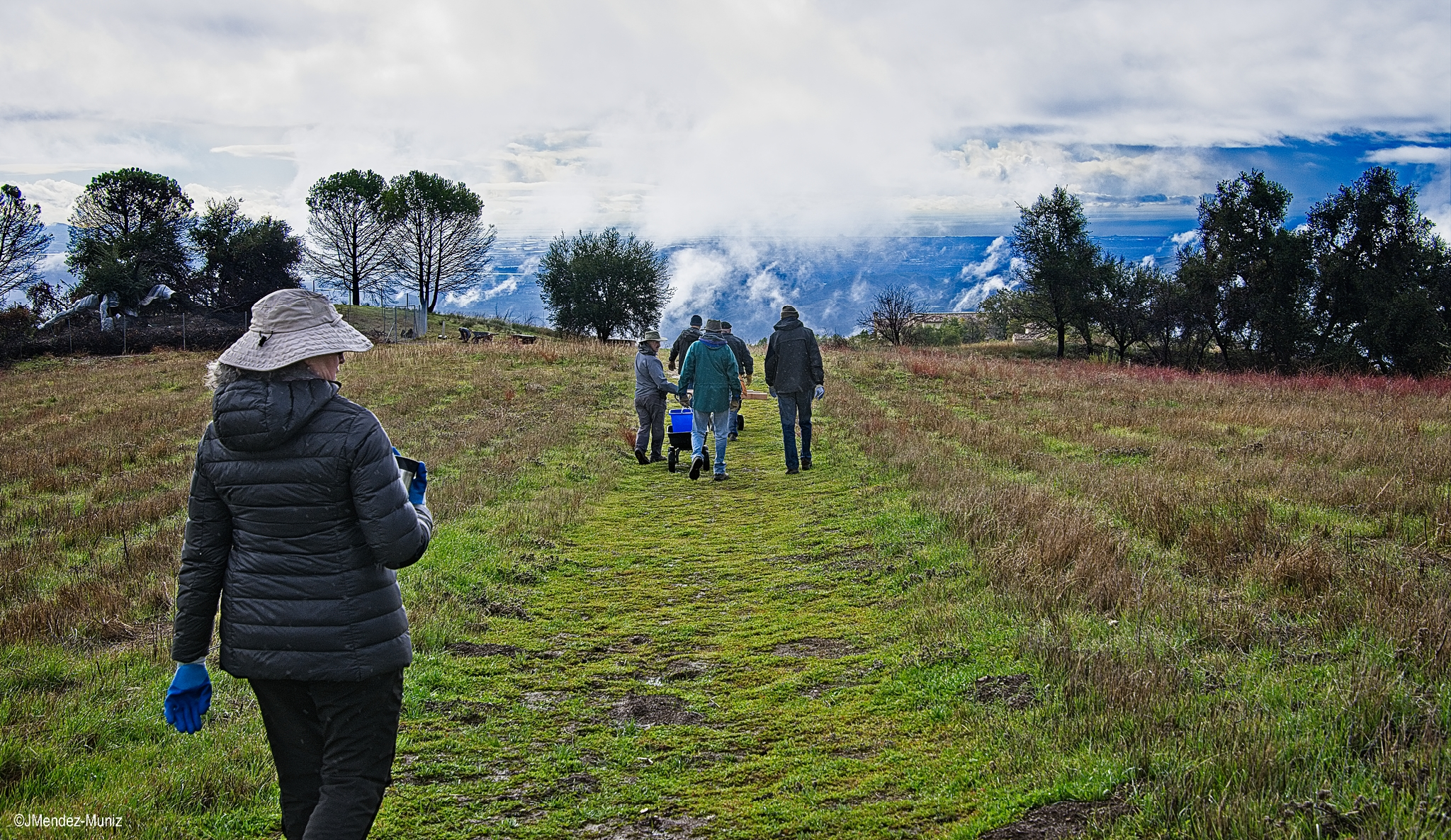 VOLUNTEERS WALKING ON BABA'S PATH to Baba's Tree (inside the seclusion fence) to harvest  dhuni  sticks at Meher Mount. The sun has just come out, and the skies were spectacular following the rainstorm. (Photo: Juan Mendez, January 12, 2019)