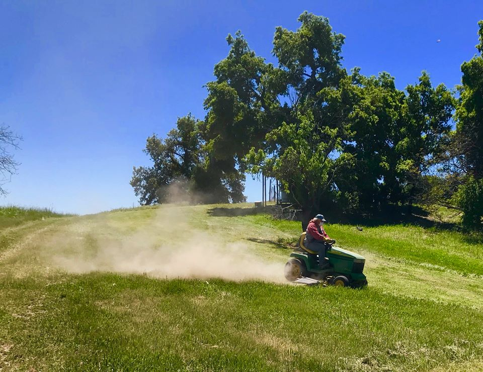 BUZZ GLASKY DRIVES the ride-on mower to begin the fire clearance process. (Photo: Ginger Glasky, April 2019)