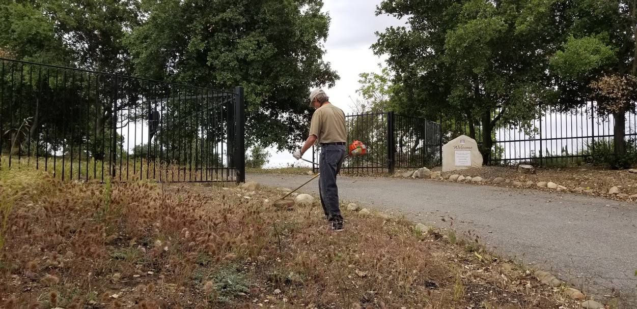 ERIC TURK uses the weed eater to clear away tall grass and weeds at the entrance to Meher Mount. (Photo: Margaret Magnus, May 19, 2019)